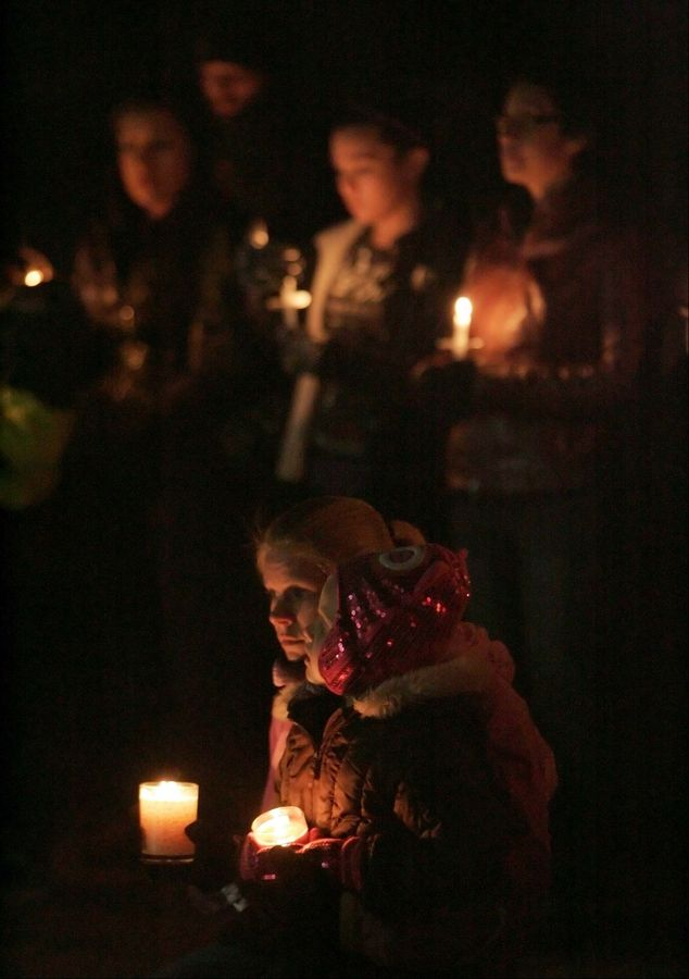 Michelle Krzmarzick of Naperville and her daughter Lucy pause during a moment of silence Friday at a vigil for 5-year-old Olivia Dworakowski at St. Thomas the Apostle Catholic Church in Naperville Friday. Police say Elzbieta Plackowska stabbed Olivia to death, along with Plackowska's seven-year-old son Justin.