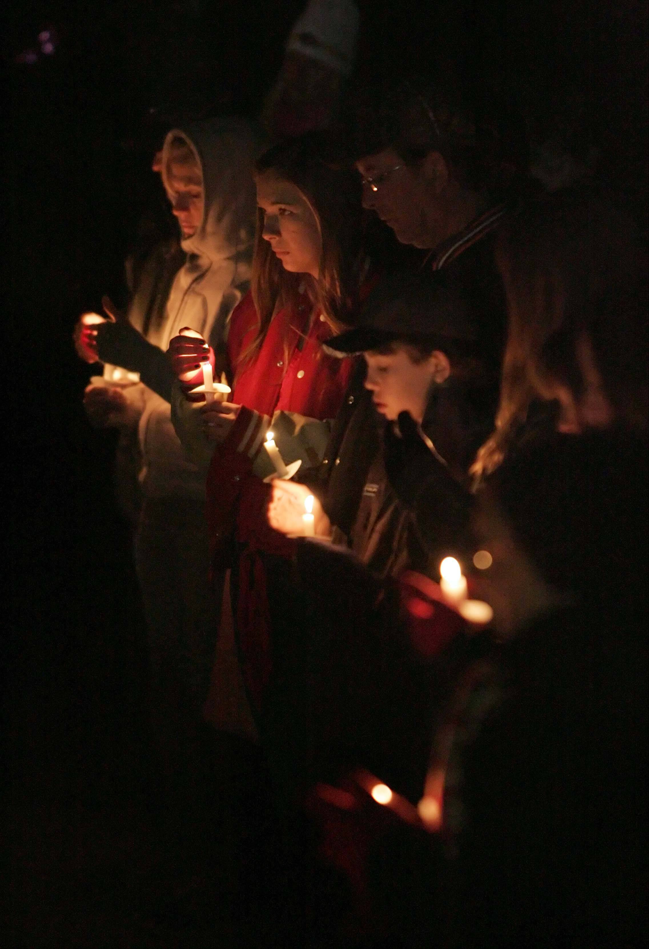 People gather during a vigil for 5-year-old Olivia Dworakowski at St. Thomas the Apostle Catholic Church in Naperville Friday. Police say Elzbieta Plackowska stabbed Olivia to death, along with Plackowska's 7-year-old son Justin.