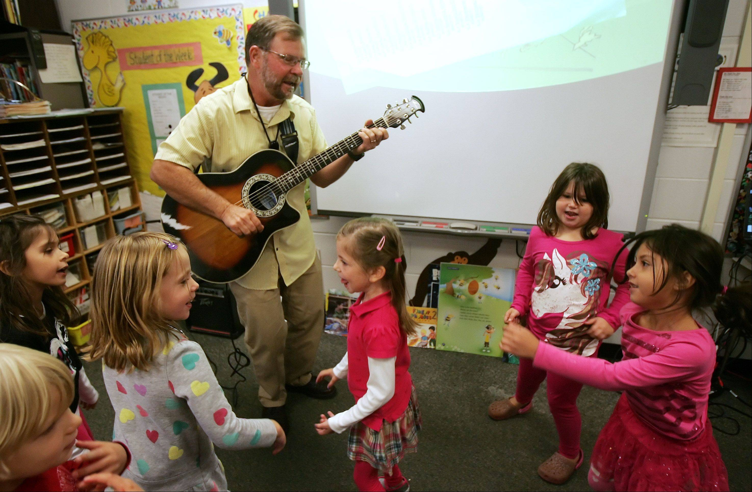"Kindergarten students dance to ""Dance Your Sillies Out"" as their teacher Tim Gapp plays guitar at North Barrington Elementary School. Gapp has been teaching kindergarten classes at the Barrington District 220 school for more than 20 years and is retiring in 2015."