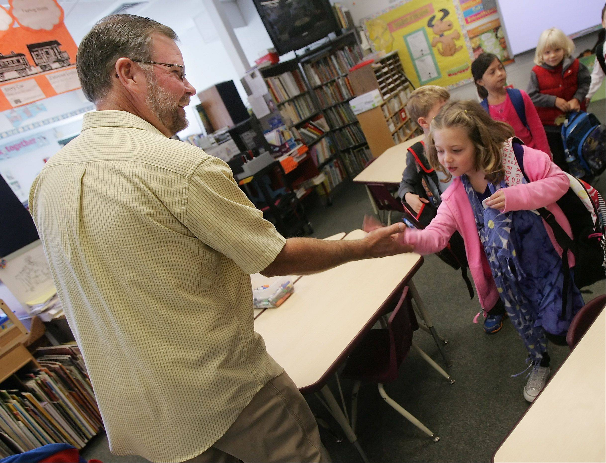 Kindergarten teacher Tim Gapp slaps hands with Madeline Lewis as he welcomes his students to his class at North Barrington Elementary School.