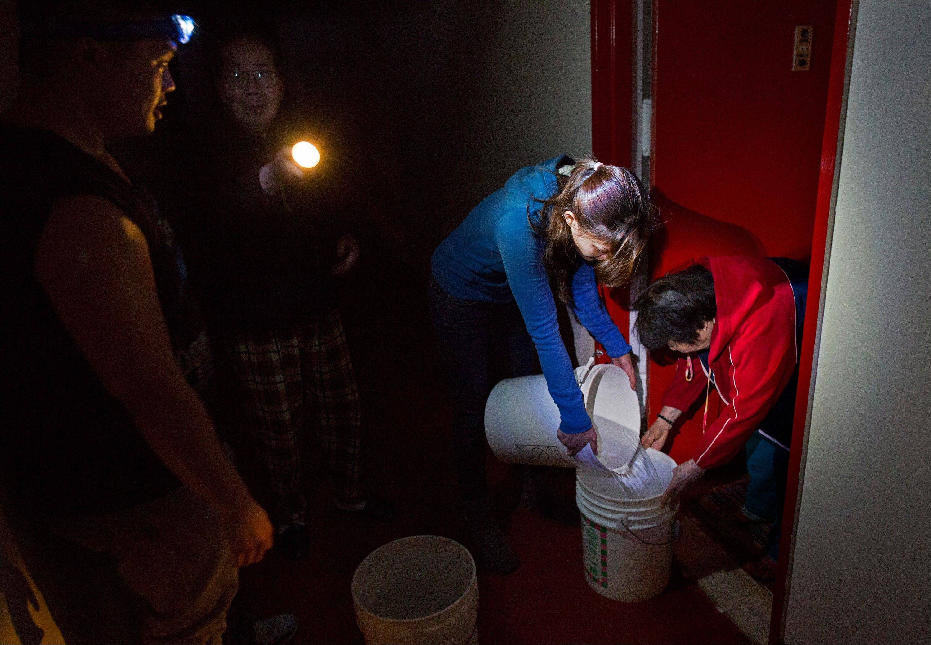 Grace Chow, 22, of New York, pours water from one bucket to another for a resident on the twentieth floor at Confucius Plaza in the Chinatown neighborhood of New York, Thursday, Nov. 1, 2012. In the wake of Superstorm Sandy, power outages have also meant loss of water for some buildings. Chow and Matthew Hom, 26, also of New York, are volunteering for the New York United Dragon and Lion Dance group.
