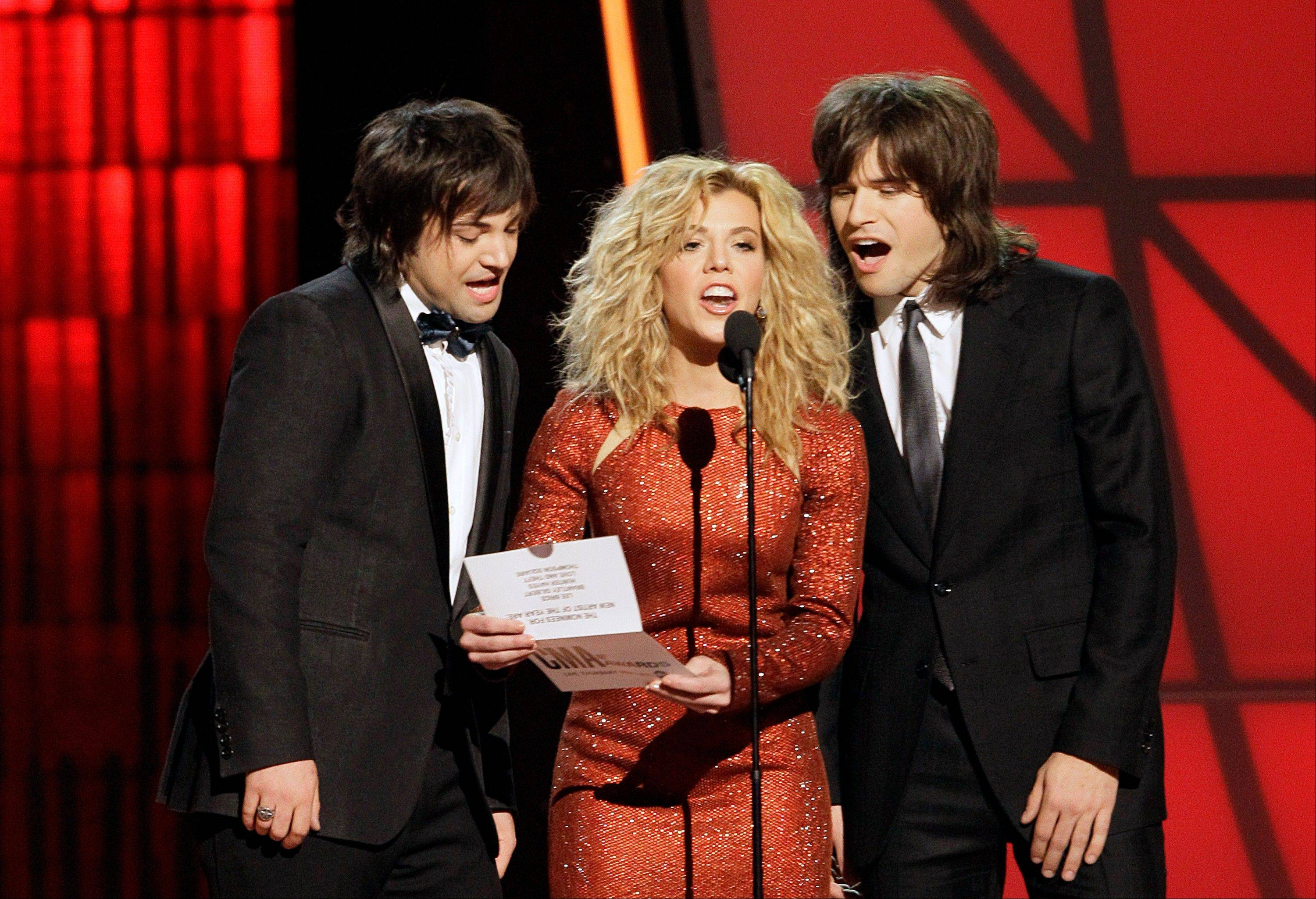 Neil Perry, left, Kimberly Perry, center, and Reid Perry, of The Band Perry, present the award for new artist of the year at the 46th Annual Country Music Awards at the Bridgestone Arena on Thursday, Nov. 1, 2012, in Nashville, Tenn.