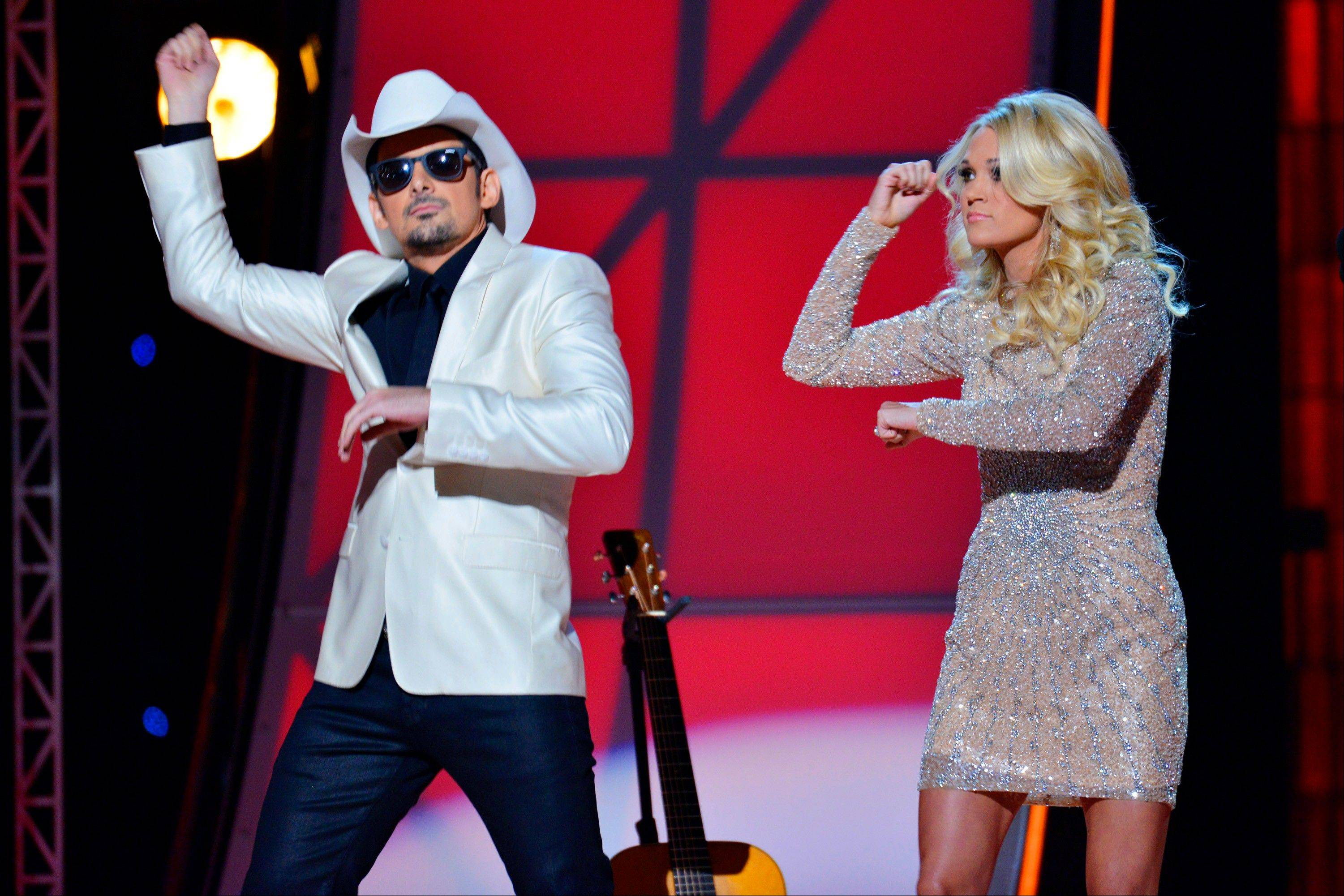 This image released by American Broadcasting Companies, Inc. shows hosts Brad Paisley, left, and Carrie Underwood as they mimic the Gangnam-style dance by South Korean rapper PSY, at the 46th Annual Country Music Awards at the Bridgestone Arena on Thursday, Nov. 1, 2012, in Nashville, Tenn.