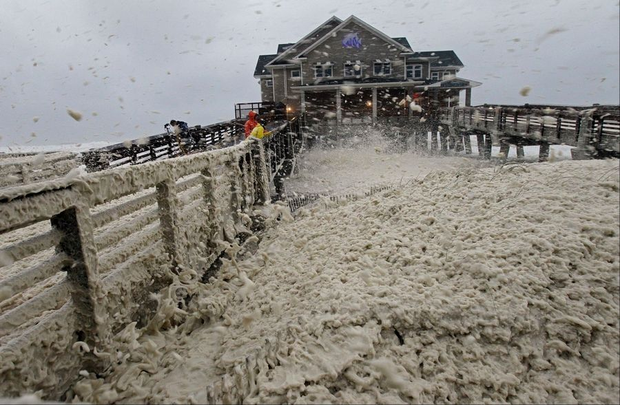 High winds blow sea foam onto Jeanette's Pier in Nags Head, N.C., on Sunday as wind and rain from Hurricane Sandy, later downgraded to a massive storm, move into the area.