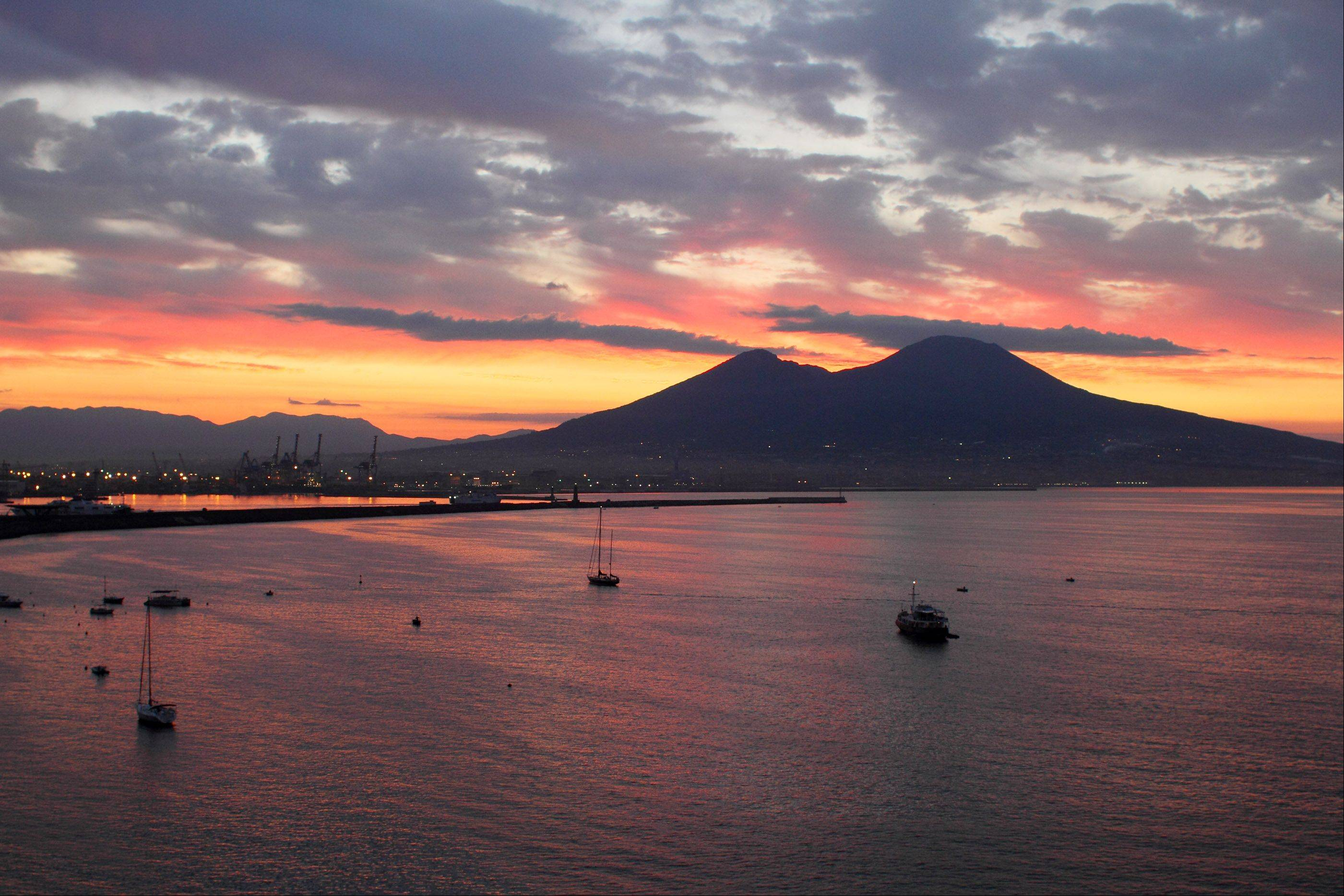This is a picture of the morning sunrise over Mt. Vesuvius in Naples, Italy taken on 9/18/12. The light scatters through the clouds and reflects the most beautiful colors over the Bay of Naples! I used a 28 mm lens on my Canon 7D.