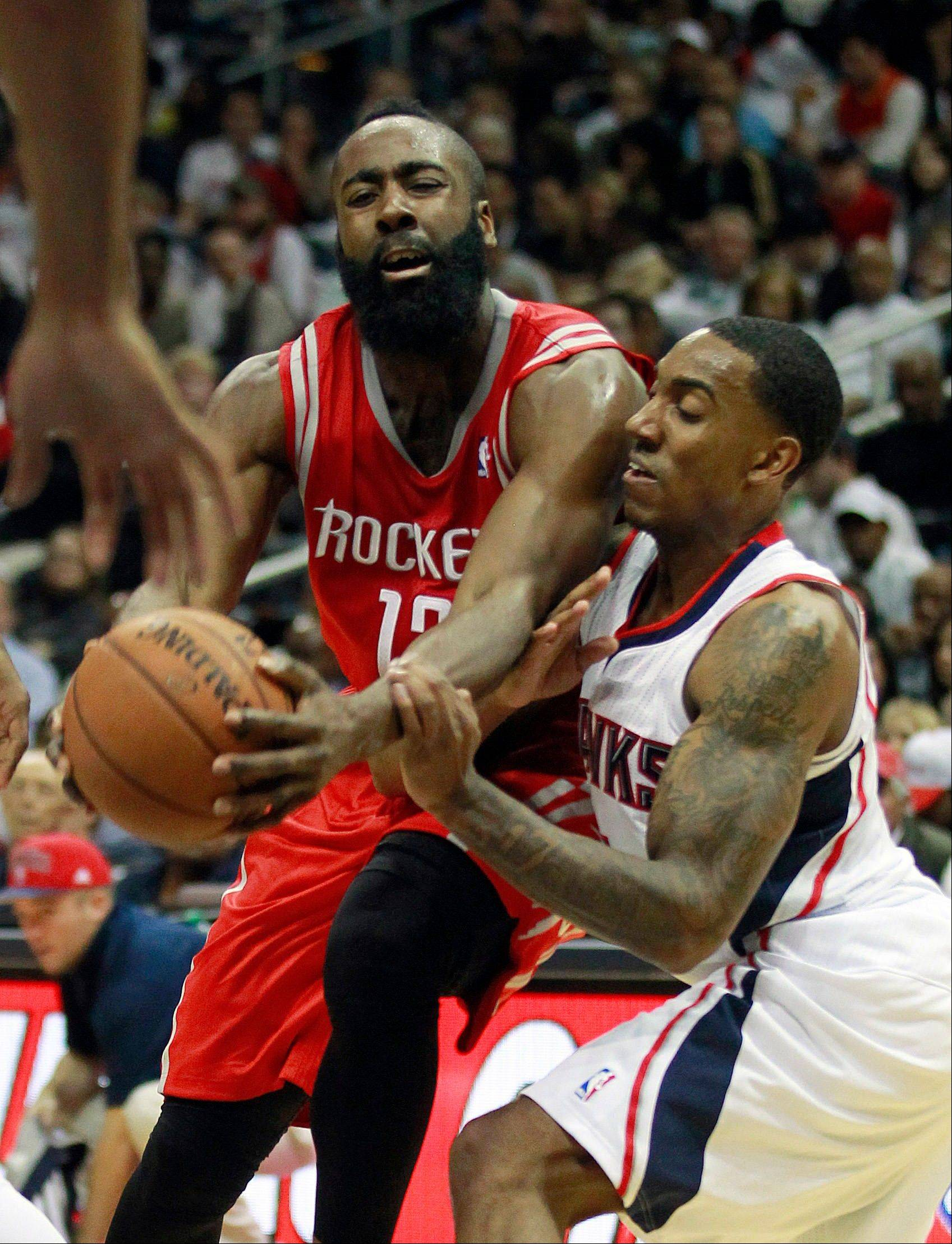 Houston Rockets shooting guard James Harden drives against Atlanta Hawks point guard Jeff Teague, right, Friday during the second half in Atlanta. Houston won 109-102.