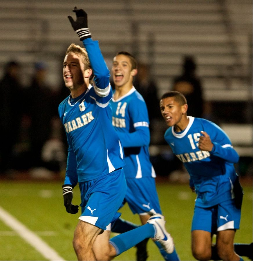 Warren's Sean Kirwan, left, celebrates his second-half goal in the Blue Devils' 3-0 win over Sandburg during the Class 3A state semifinal match held at Lincoln-Way North High School. Also celebrating are Nick Haas (14) and Elijah Parker (15).