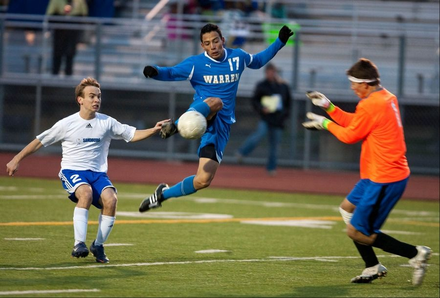 Warren's Rafa Macias, middle, fires a shot wide of the Sandburg net during Class 3A boys soccer state semifinal play at Lincoln-Way North.