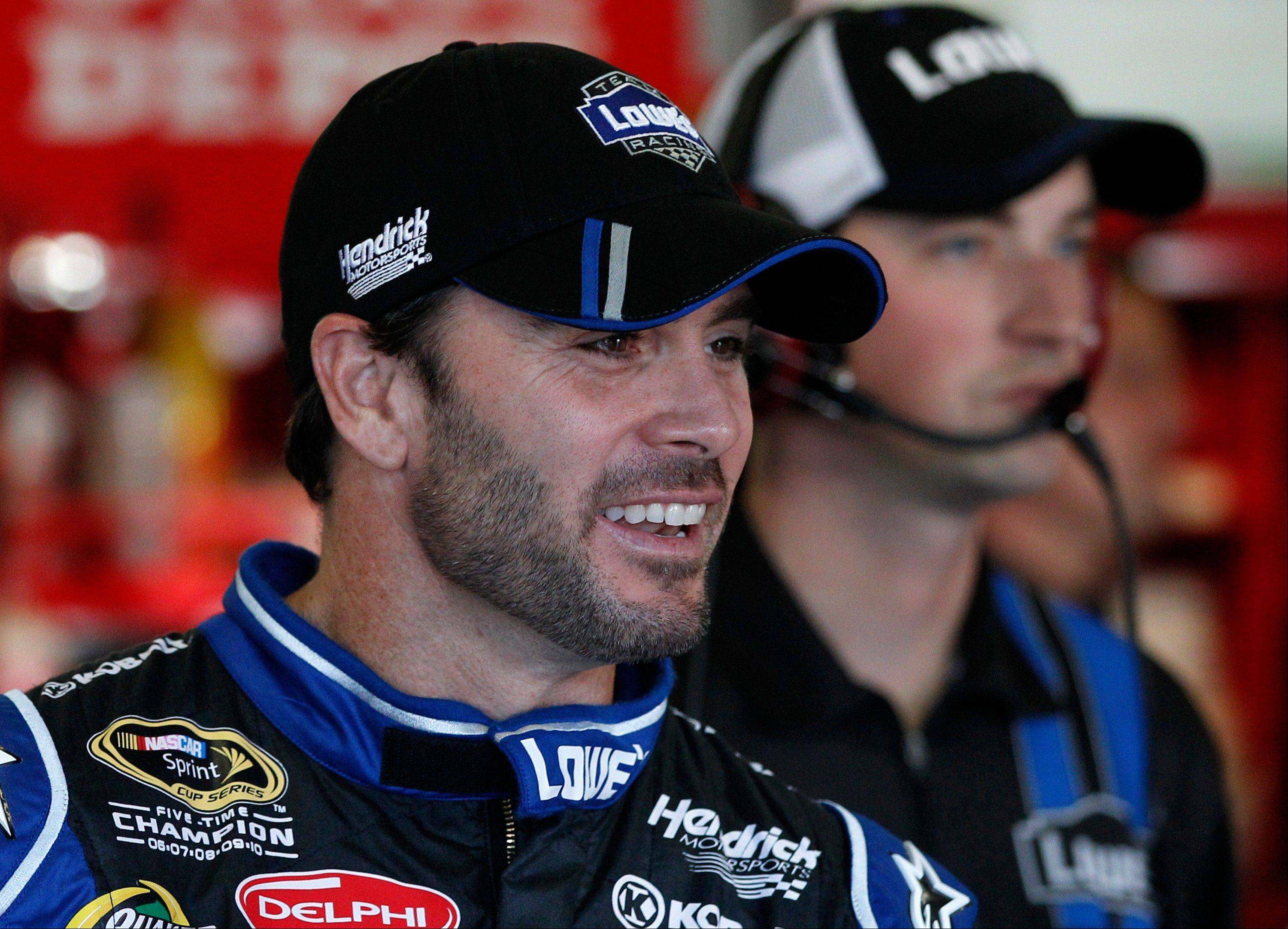 Driver Jimmie Johnson smiles as he talks with crew members in the garage Friday before a practice for Sunday's NASCAR Sprint Cup Series AAA Texas 500 auto race at Texas Motor Speedway in Fort Worth, Texas.