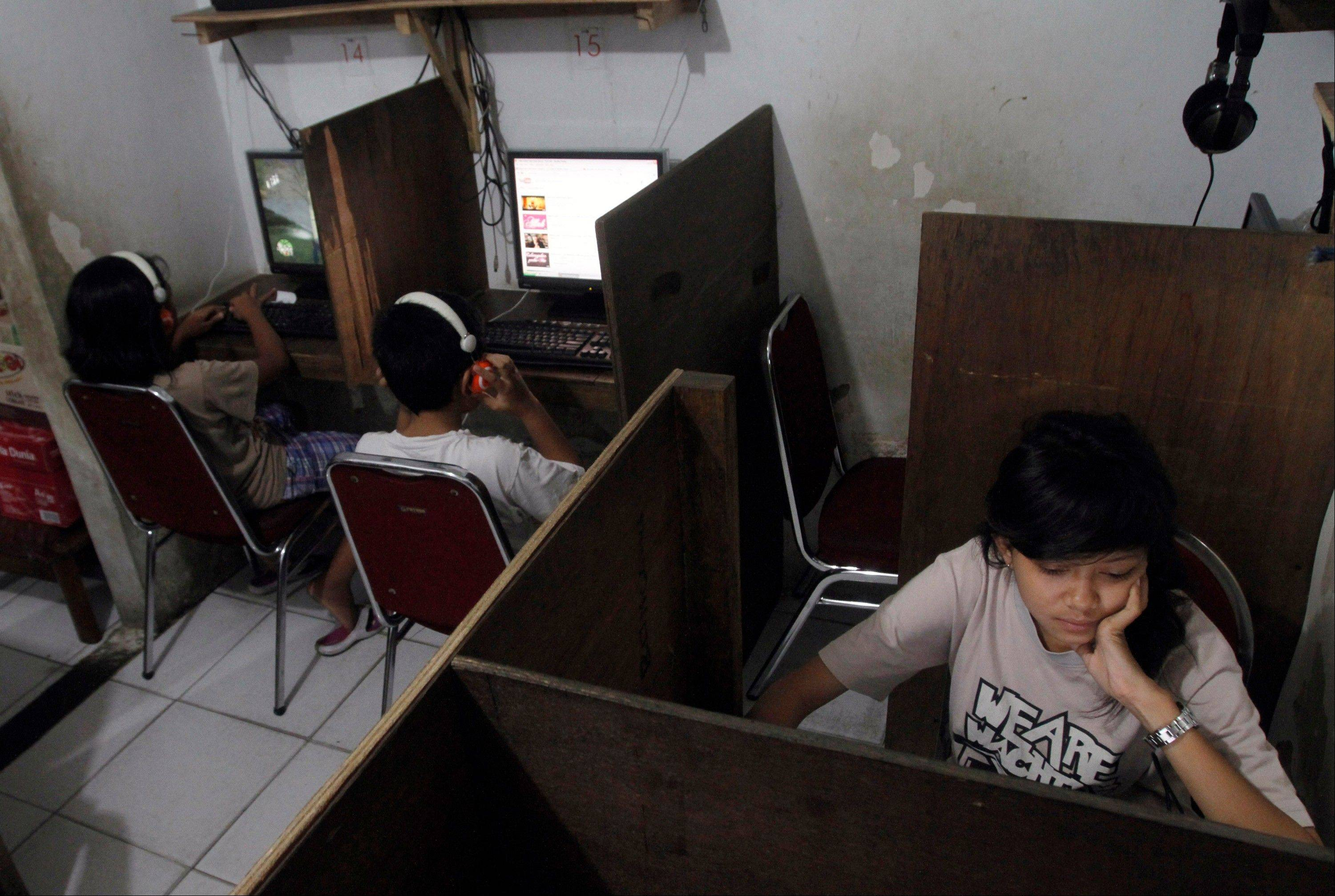 In this Friday, Oct. 19, 2012, photo, Indonesian youths browse at an internet cafe in Jakarta, Indonesia. There are growing numbers of incidents involving internet social media networks being used as a mean for children trafficking in Indonesia, at least eight reported this month alone of young girls being abducted and enslaved by men who approached them randomly on Facebook, raising concerns that the overall number of trafficked children remains grossly underestimated in the sprawling archipelago of 240 million.