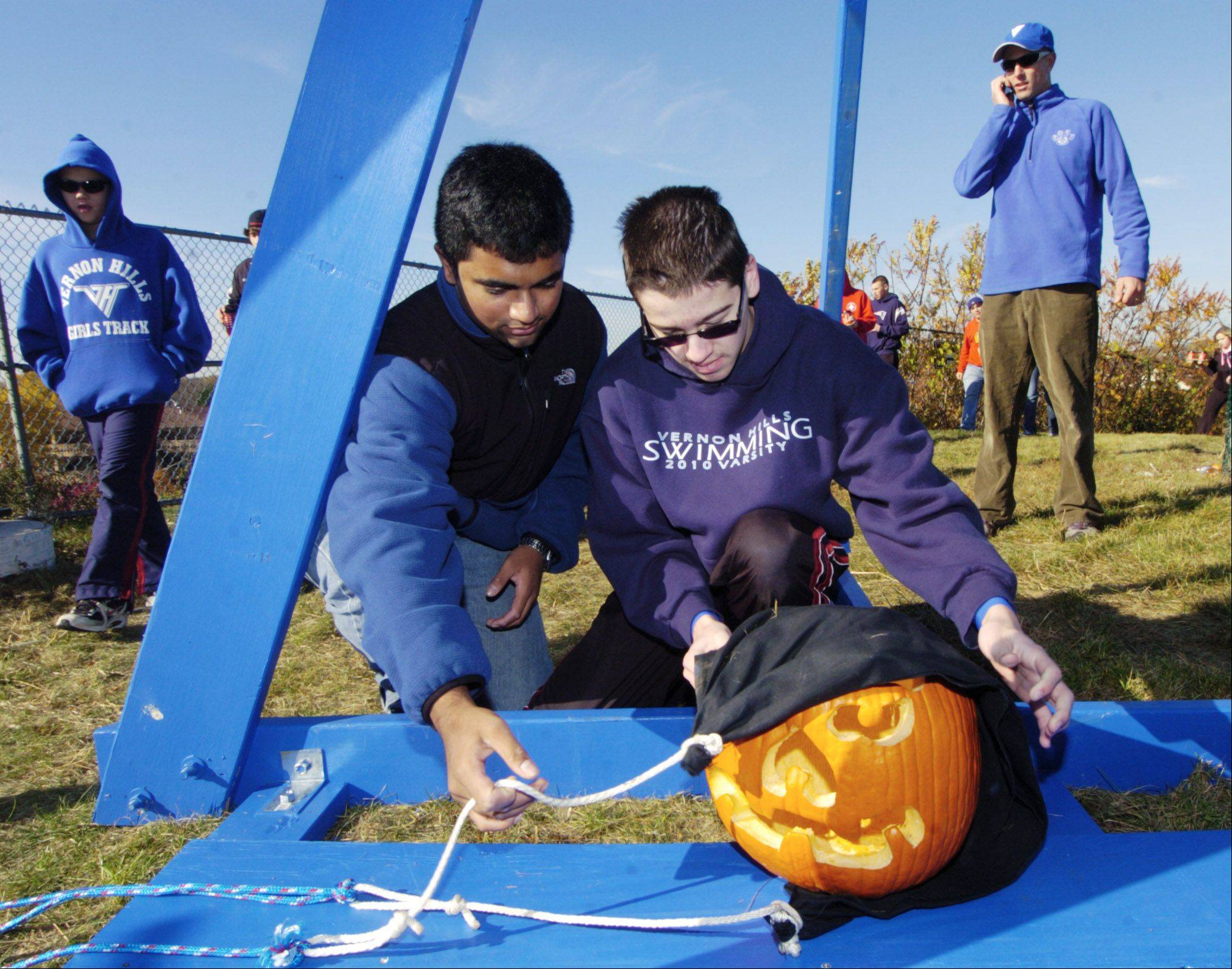 Alex Mathew, left, and Nic McAdams load a jack-o'-lantern onto the trebuchet during a previous pumpkin launch at Century Park in Vernon Hills.
