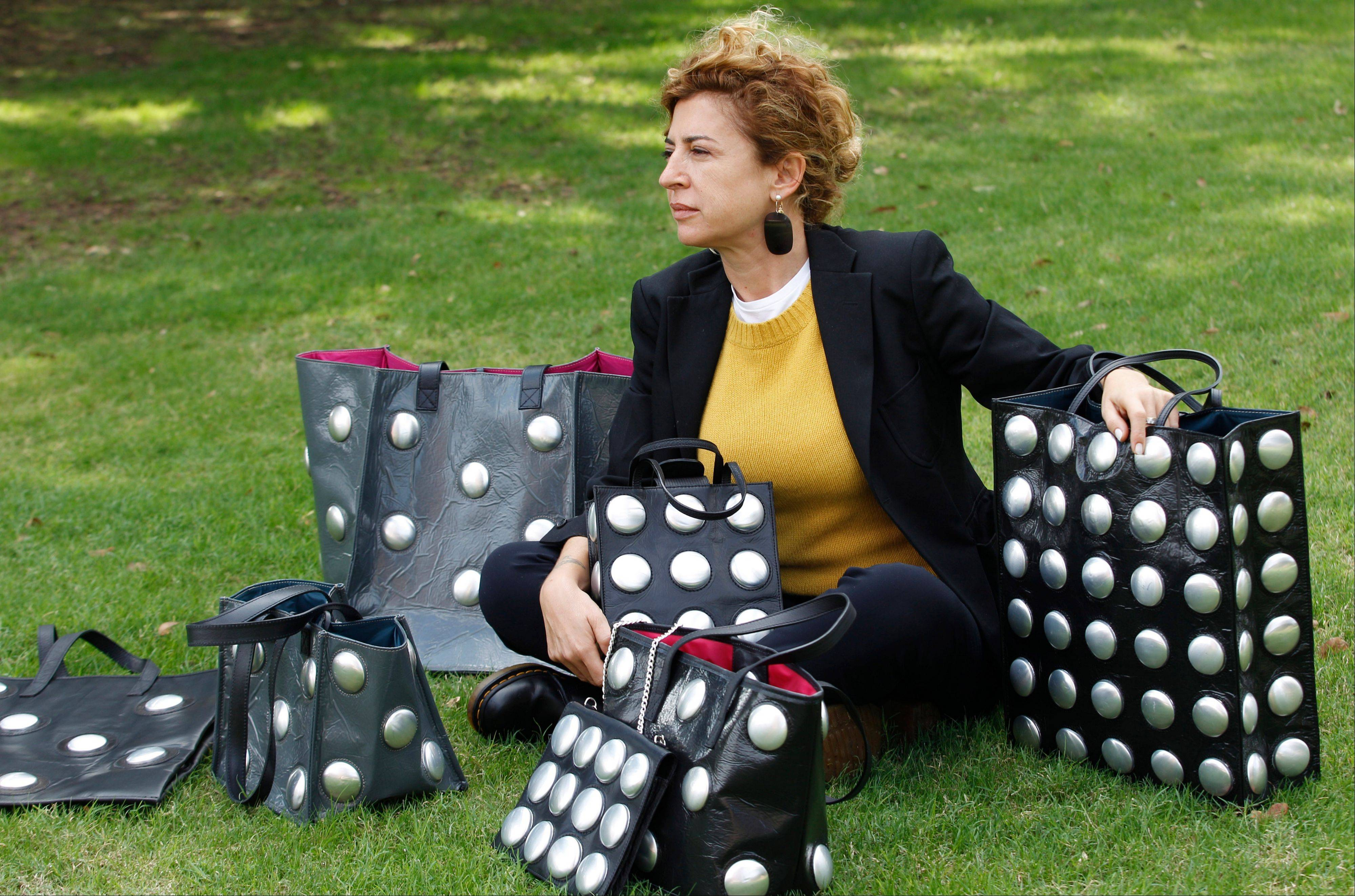 This Oct. 24, 2012 photo shows Ilaria Venturini Fendi, a member of the famous fashion family, posing with bags from her Carmina Campus fashion project that produces bags from repurposed materials in Dallas. The bags shown are made of garbage bags and soda cans.