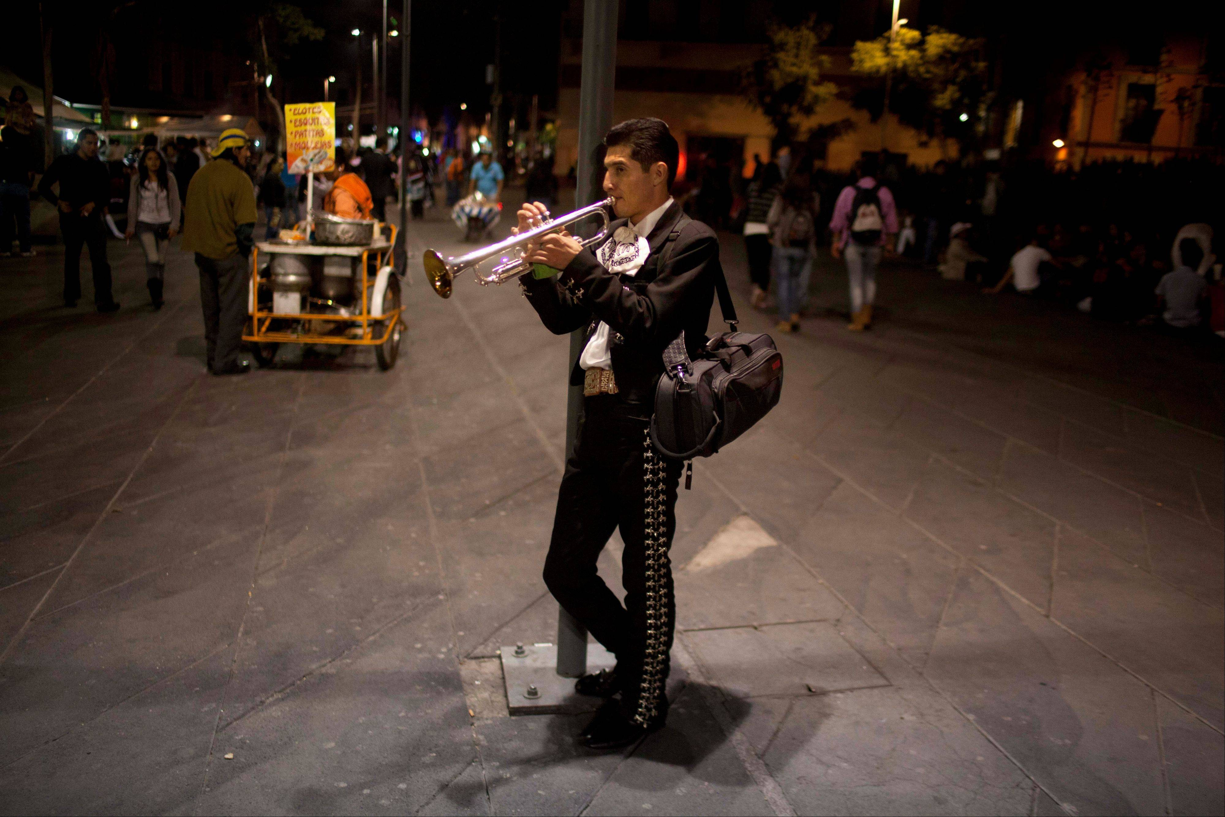 In this October 2012 photo, professor at the Mariachi School Ollin Yoliztli, Eduardo Sanchez Ortiz, practices as he waits for clients at Plaza Garibaldi in Mexico City. The new mariachi school in Mexico City is seeking to revive a music that�s lost ground over the years. The school, whose name means life and movement in indigenous Nahautl, teaches folk bands how to play professionally while grooming a new generation of songwriters and composers.