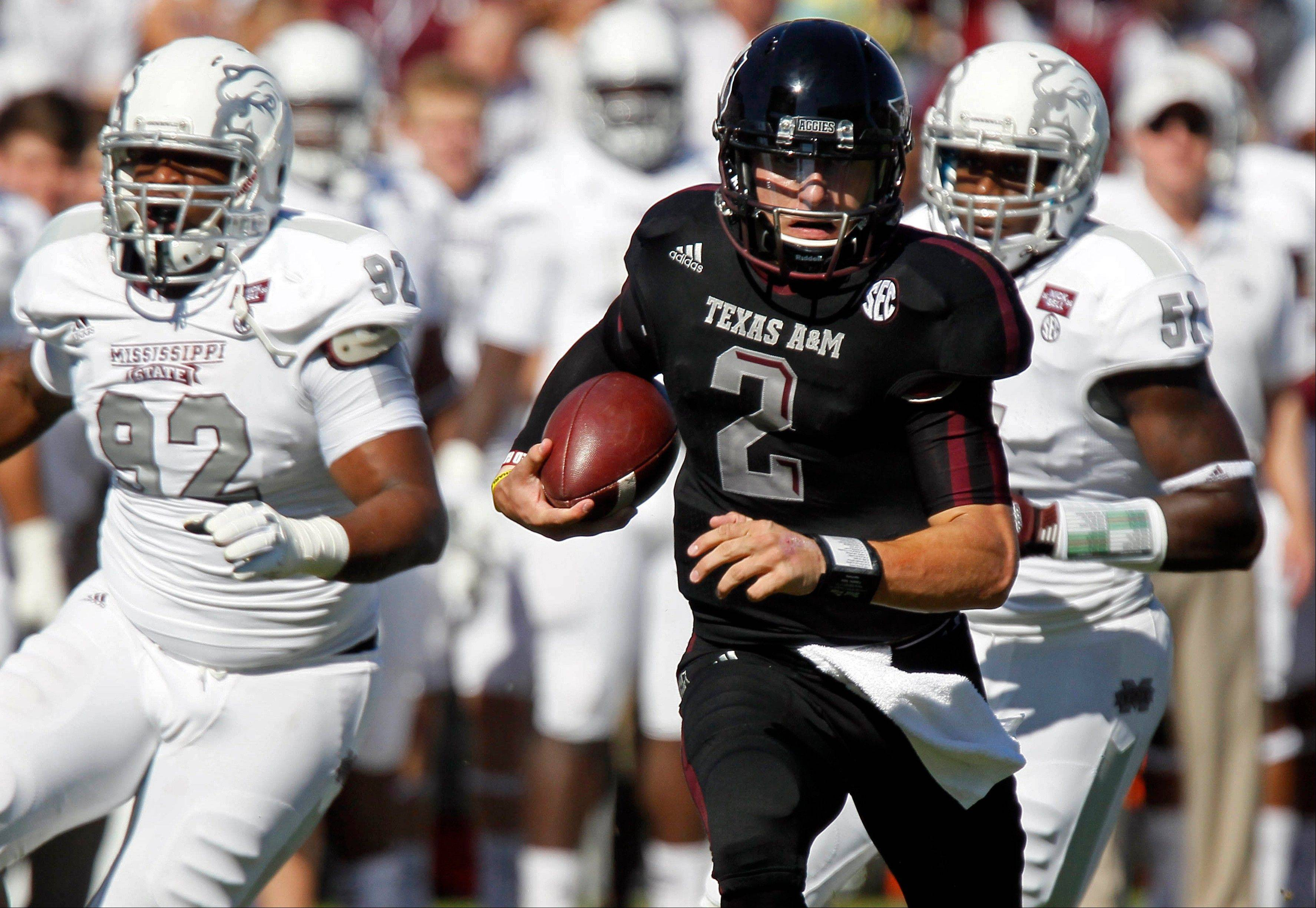 Texas A&M quarterback Johnny Manziel runs past Mississippi State defensive lineman Kaleb Eulls and other defenders for a touchdown Saturday during the second quarter in Starkville, Miss.