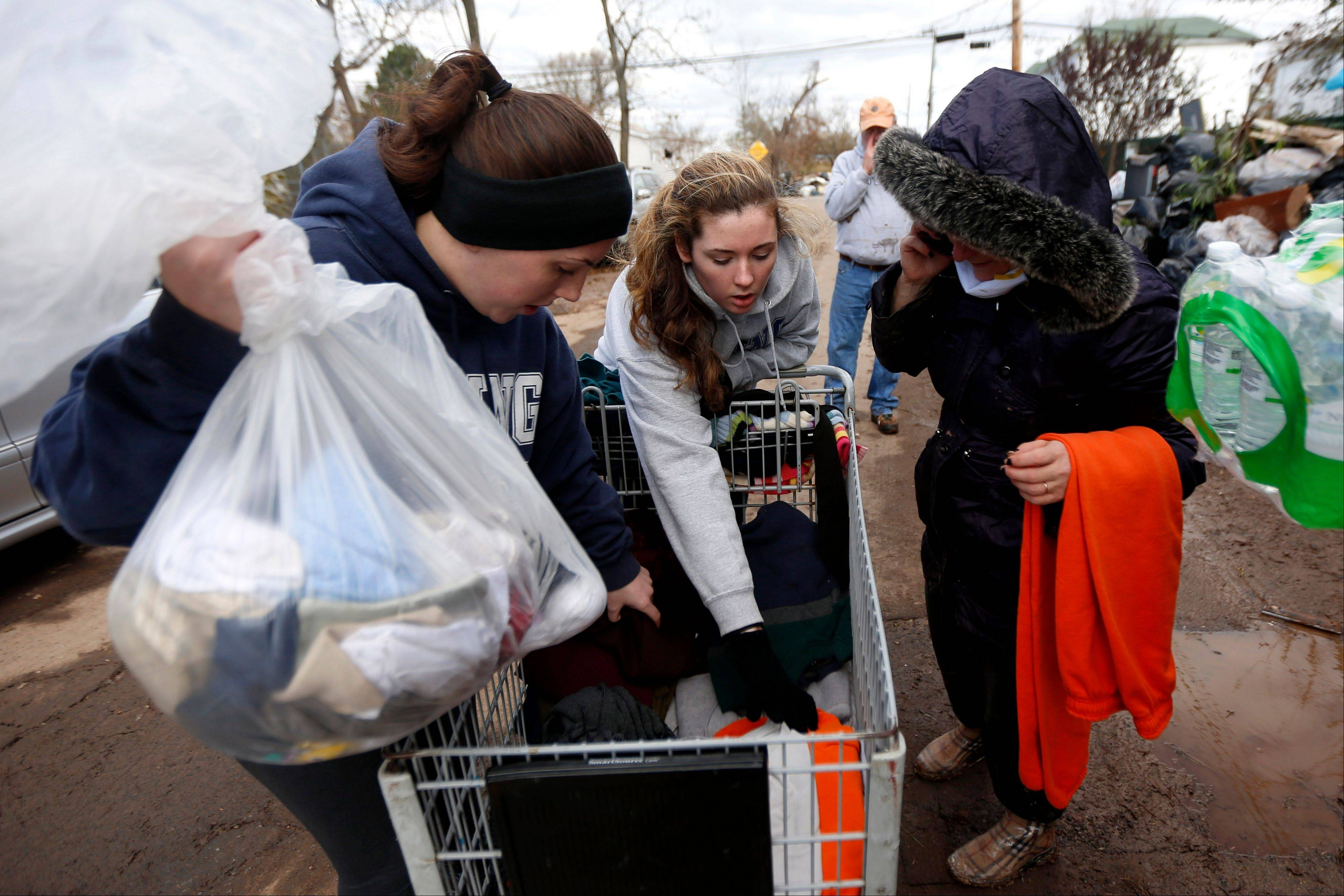 Associated Press Volunteers Laurie McLoughlin, left, and her sister Caitlin McLaughlin, center, sort through clothing Saturday to donate to a resident.