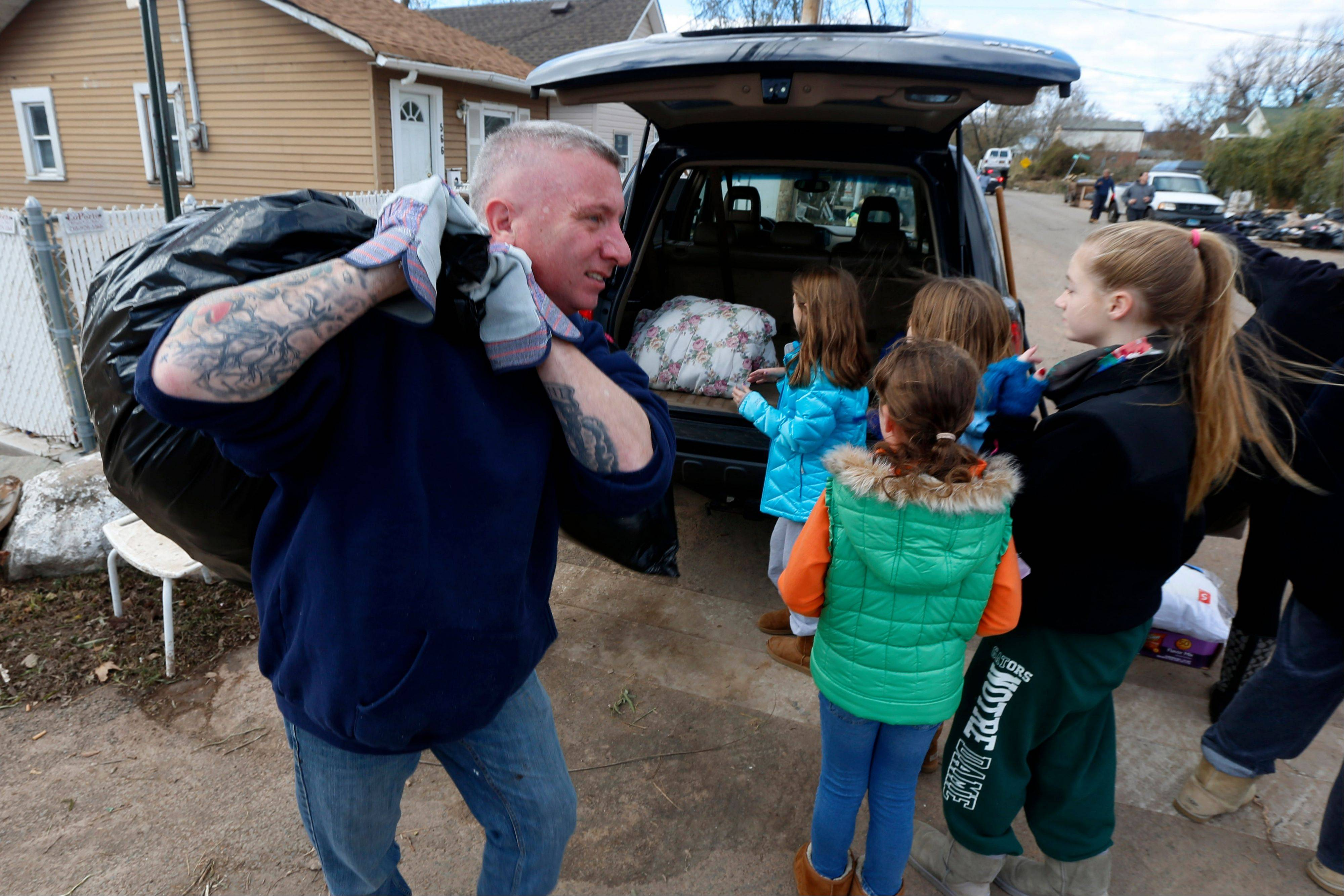 Associated Press Volunteer Mike Giuliano, left, carries a bag of clothing to be donated to residents affected by Superstorm Sandy.