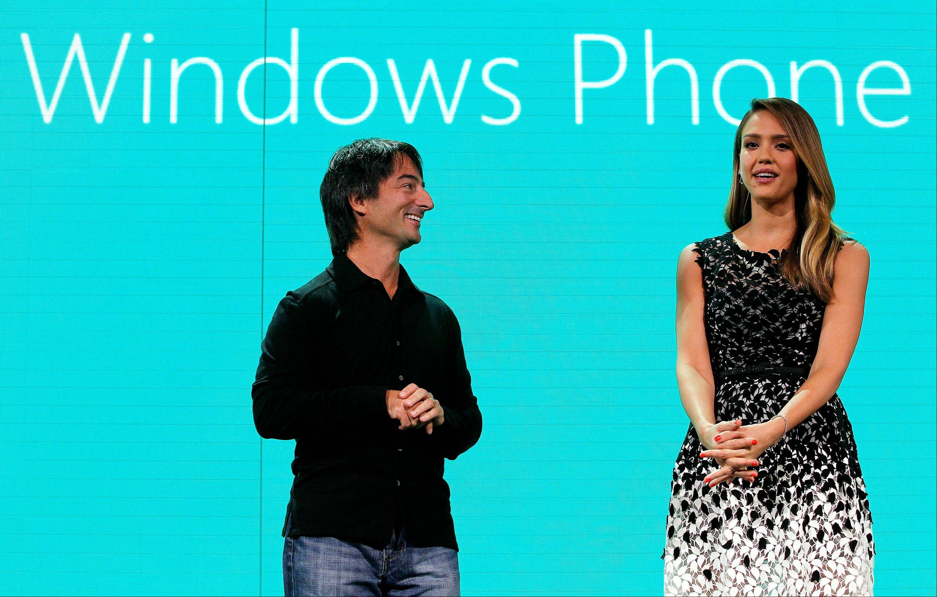 Joe Belfiore, vice president at Microsoft Corp., left, listens to actress Jessica Alba speak Monday at an event to unveil Windows Phone 8 software in San Francisco, California.