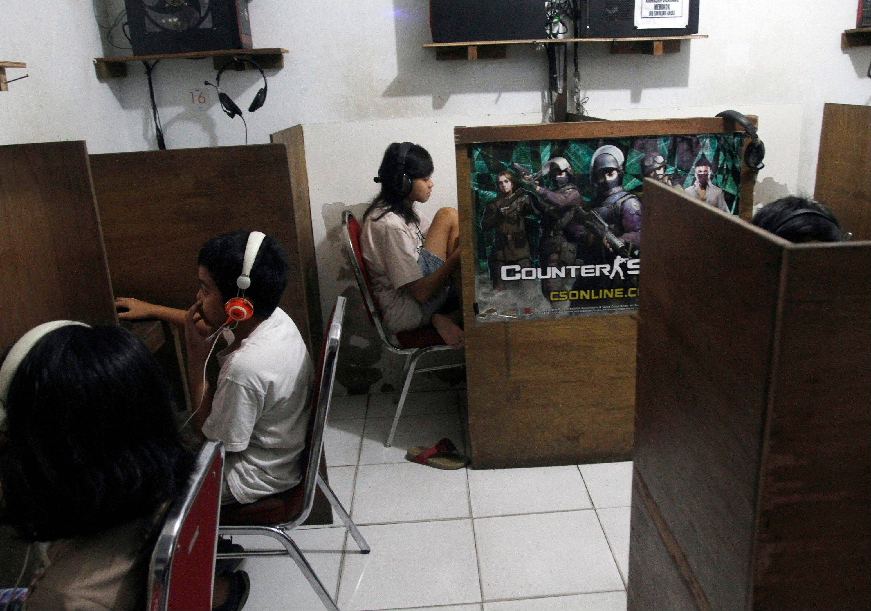 In this Friday, Oct. 19, 2012 photo, Indonesian youths browse at an internet cafe in Jakarta, Indonesia. There are growing numbers of incidents involving internet social media networks being used as a mean for children trafficking in Indonesia, at least eight reported this month alone of young girls being abducted and enslaved by men who approached them randomly on Facebook, raising concerns that the overall number of trafficked children remains grossly underestimated in the sprawling archipelago of 240 million.