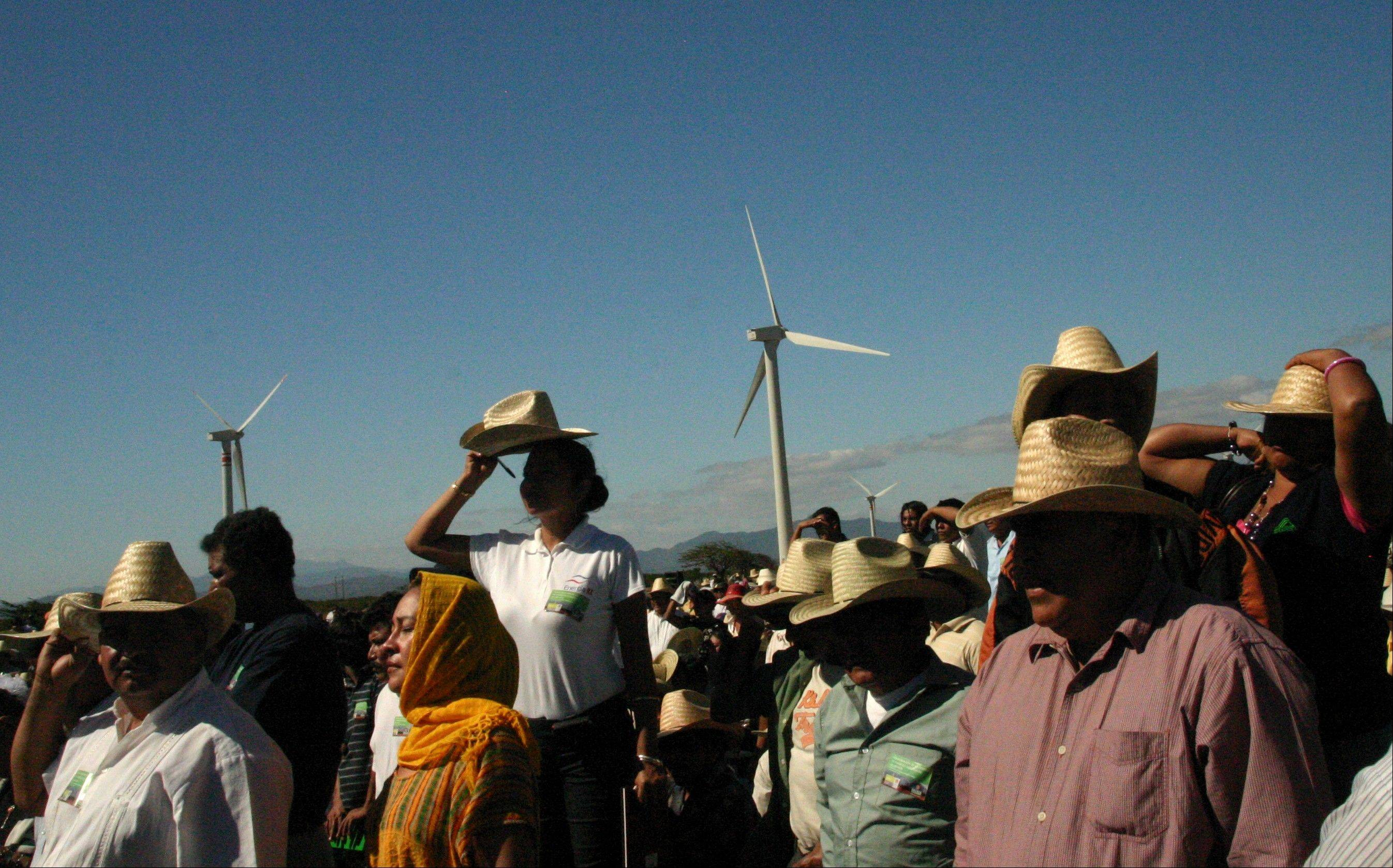 In this January 2009 photo, people watch during the inauguration of a new $550 million wind farm project in La Ventosa, Mexico, located on the narrow isthmus between the Gulf of Mexico and the Pacific Ocean. Mexican President Felipe Calderon has made the inauguration of wind parks one of the main focuses of his administration's ambitious pledge to cut Mexico's carbon emissions by 30 percent by 2020, and once again Tuesday as he has done before, he stopped in the state of Oaxaca to inaugurate a new clutch of wind turbines.