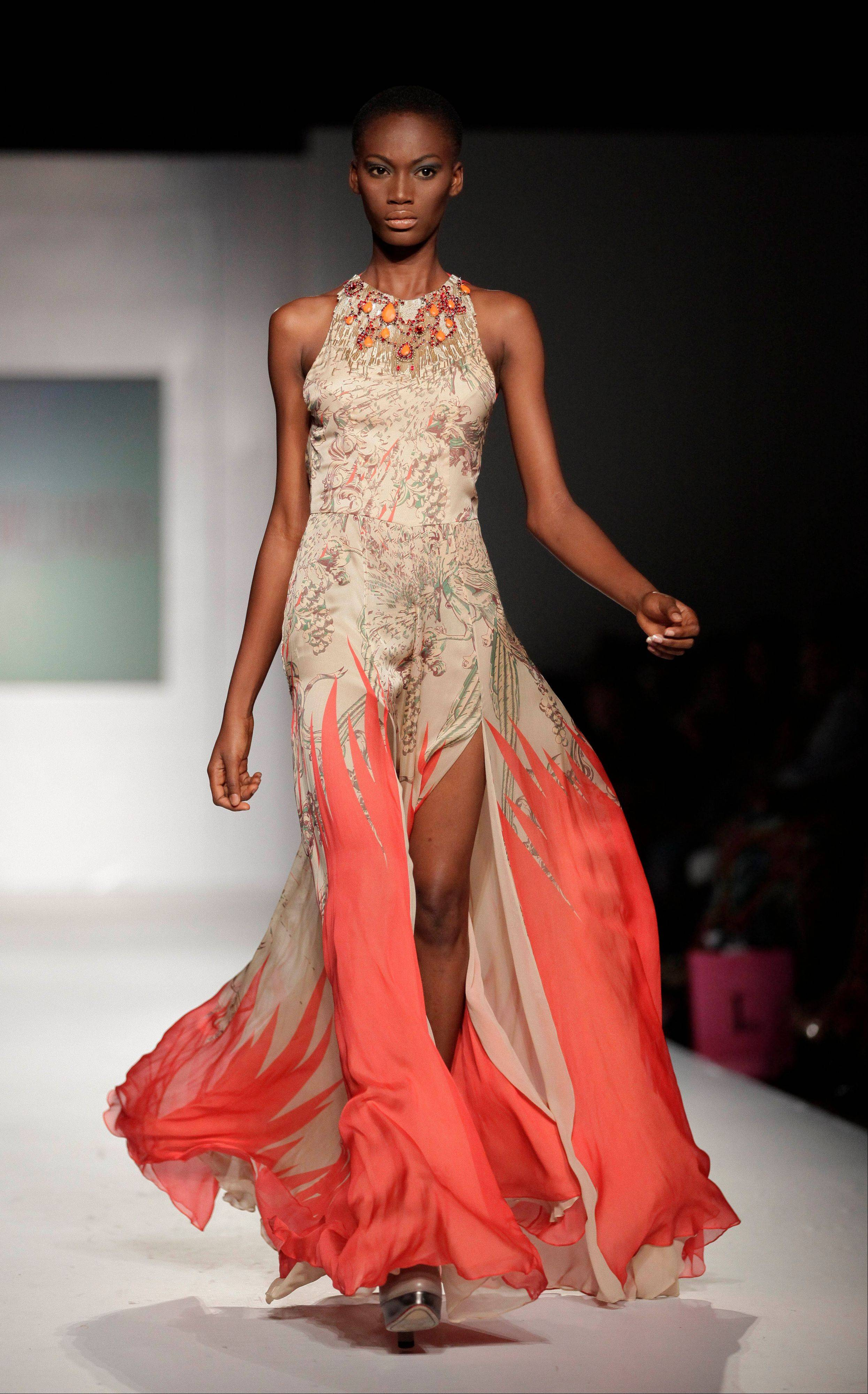 In this photo taken Saturday, Oct. 27, 2012, a model displays an outfit by British designer Matthew Williamson in Lagos, Nigeria. Some international high-end fashion buyers are looking beyond Nigeria's bleak headlines to uncover the next big new thing, fun and glamour through its use of print and color, characteristics which have come to define the vibrant local fashion scene.