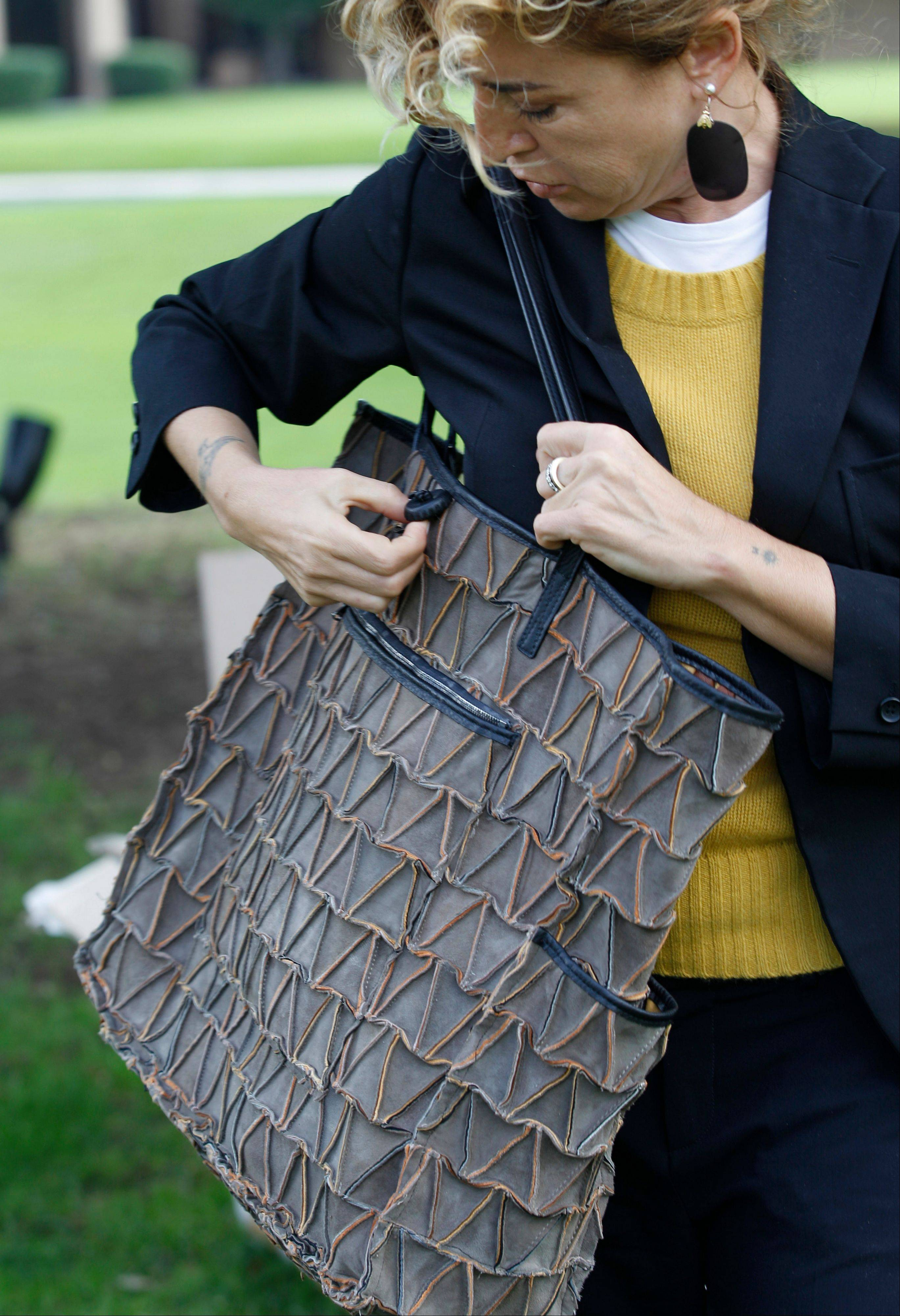 This Oct. 24, 2012 photo shows Ilaria Venturini Fendi, a member of the famous fashion family, inspects a bag from her Carmina Campus fashion project that produces bags from repurposed materials in Dallas. The bags shown are made of garbage bags and soda cans.
