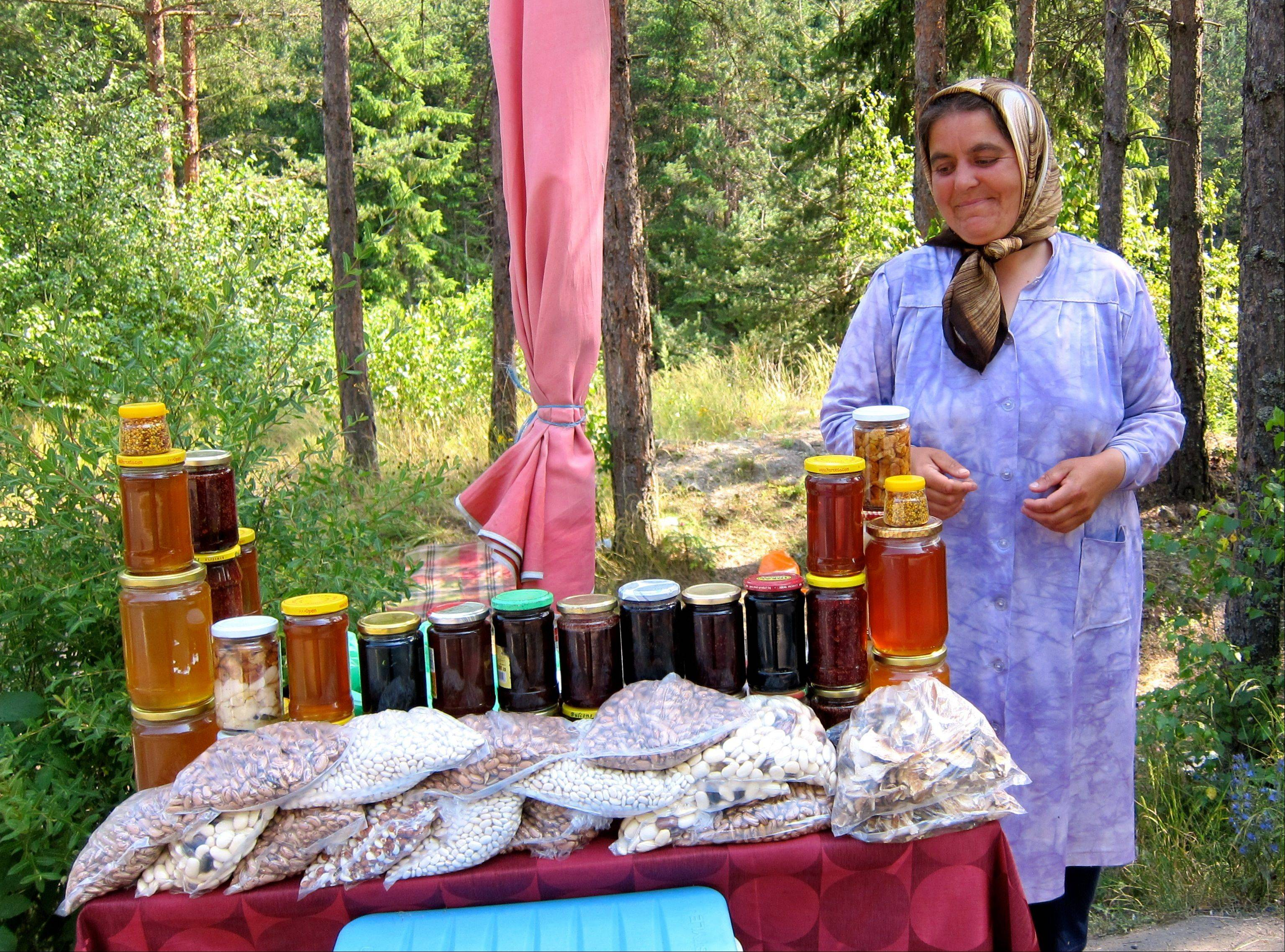 A woman sells honey at a roadside stand in Bulgaria.