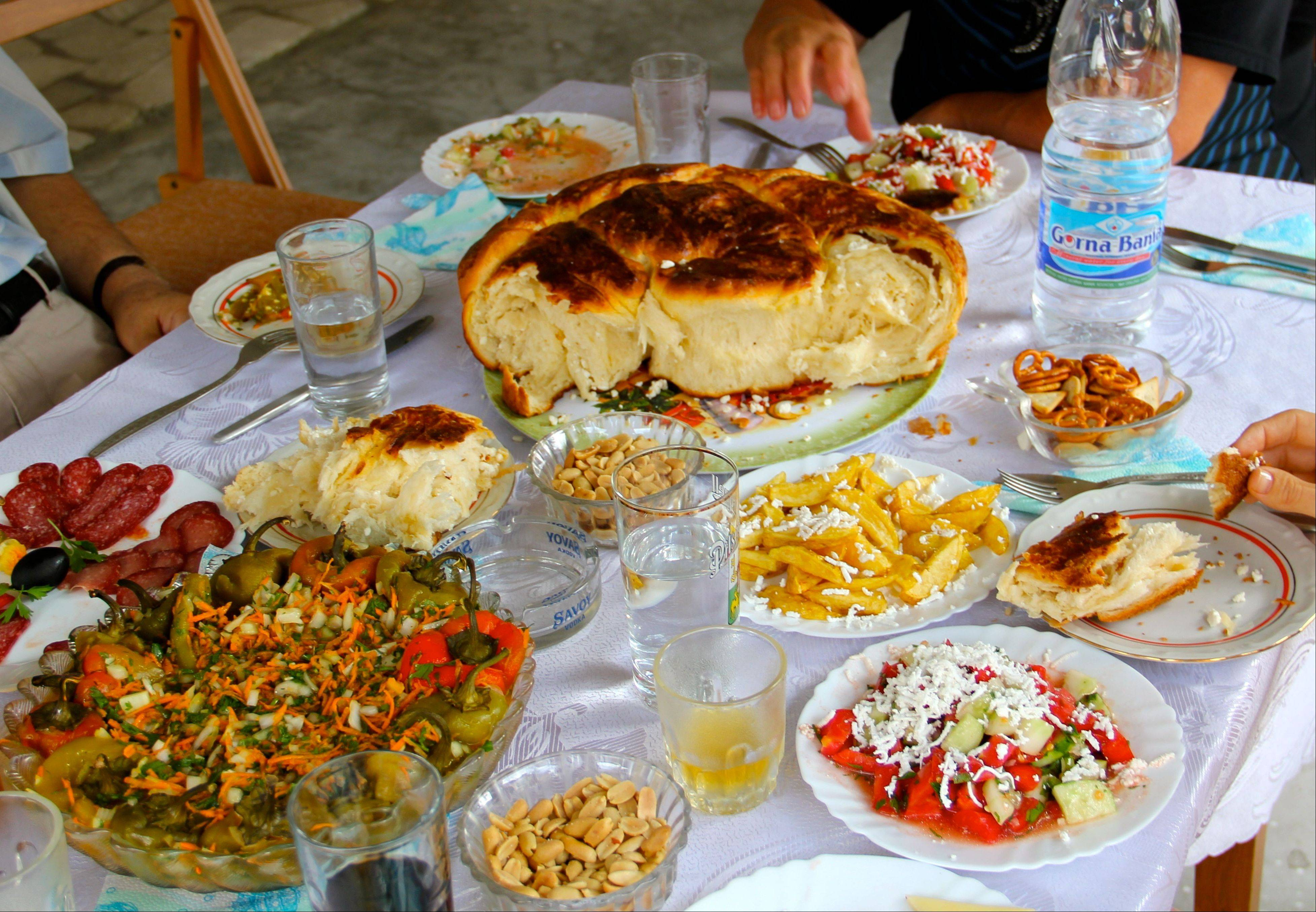 A traditional Bulgarian feast includes shopska salad, lower right, a salad of peppers and a bread with feta cheese called pogatcha.