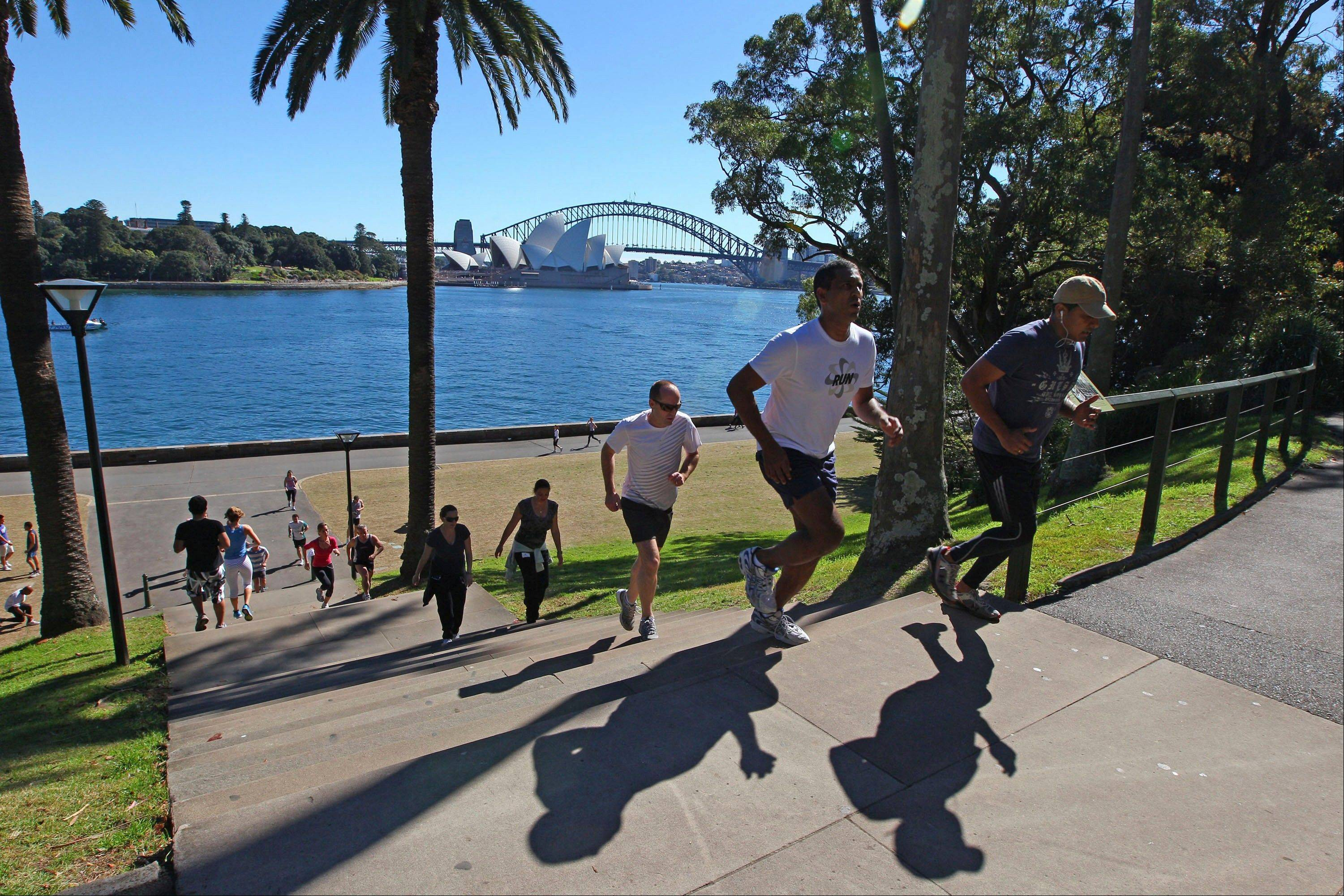 People run up and down stairs in a park adjacent to the Sydney Opera House and Harbour Bridge in Sydney.