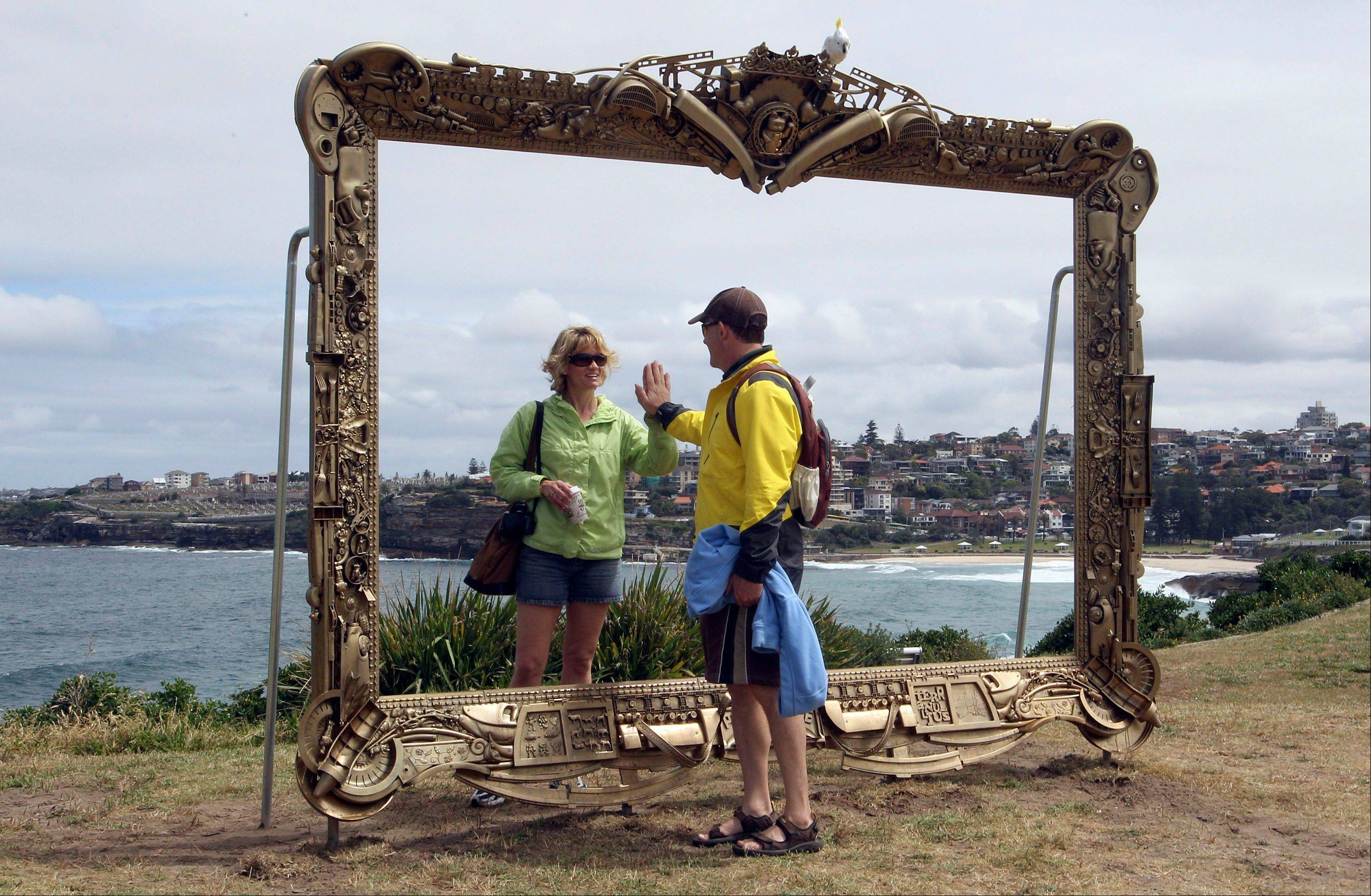A couple pretend to be a mirror image of each other in Jane Gilling's sculpture, Provenance at Sculptures By The Sea in Sydney. Every November, the popular exhibition features large art installations placed along the path and beaches, providing a free seaside art show.
