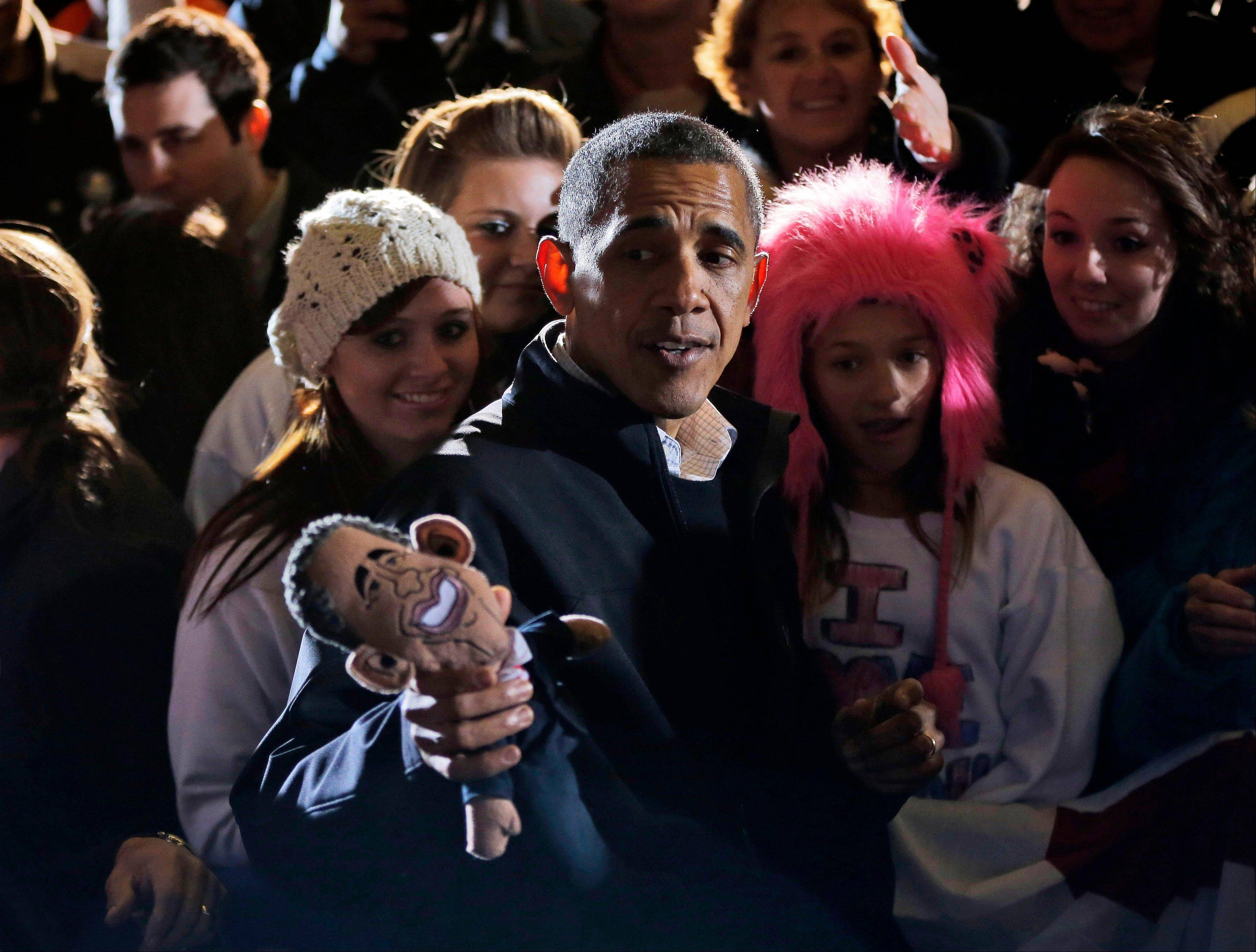 President Barack Obama holds up a doll bearing his resemblance, which was given to him Saturday by a supporter, at a campaign event at Washington Park in Dubuque, Iowa.