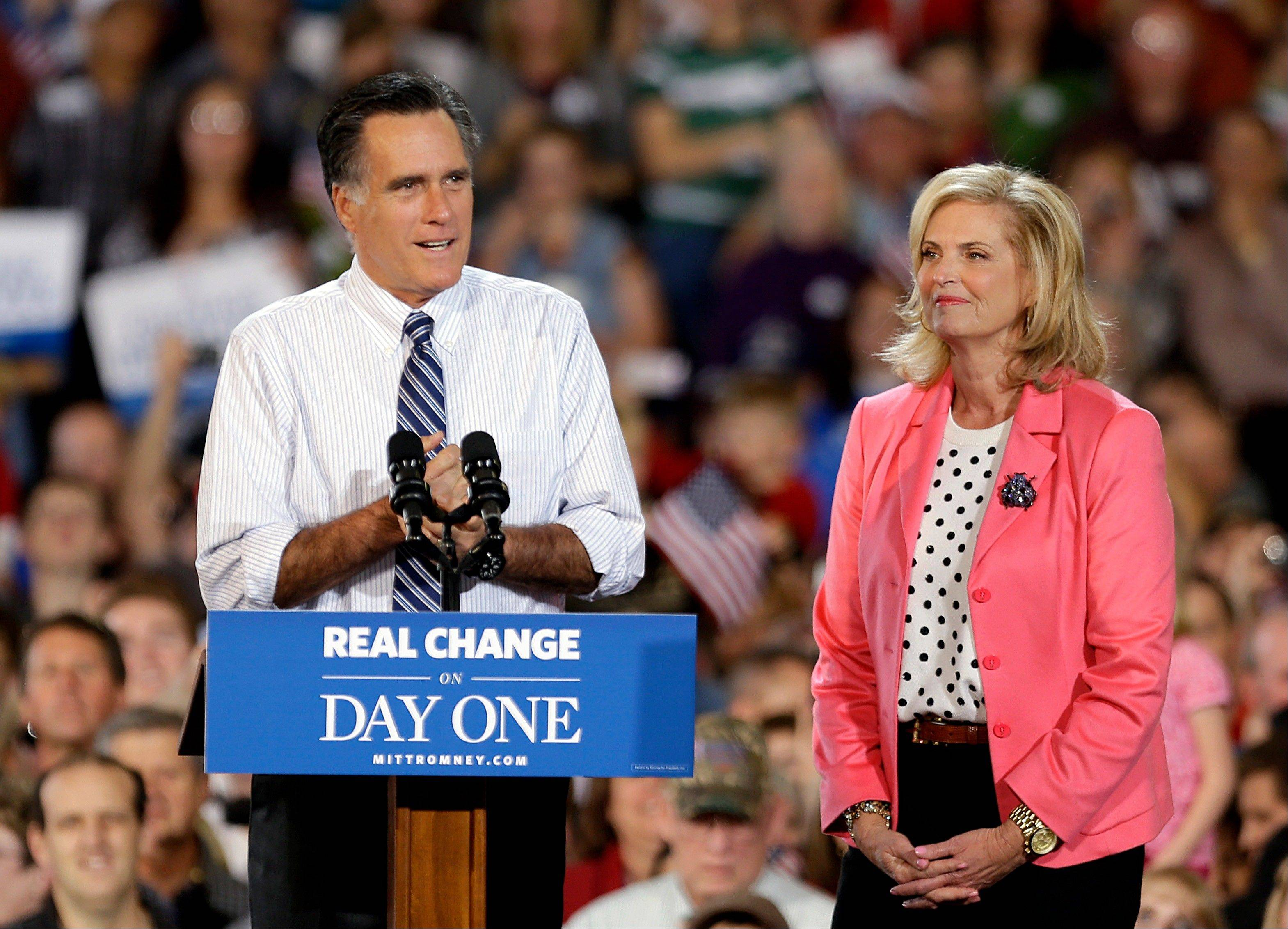Republican presidential candidate, former Massachusetts Gov. Mitt Romney, left, steps to the podium Saturday after being introduced by his wife Ann, at a campaign event at Colorado Springs Municipal Airport.