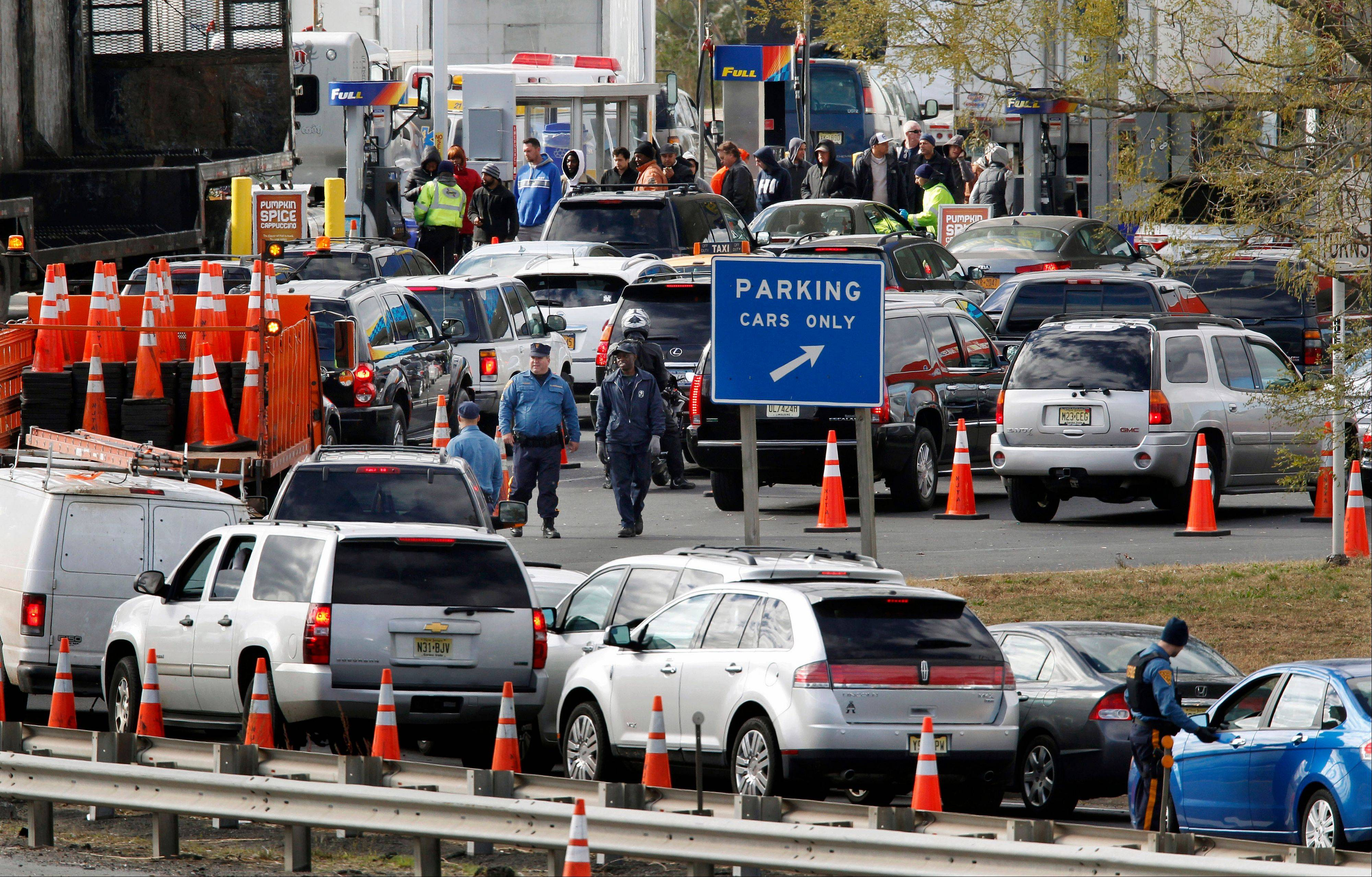 New Jersey state troopers keep order as motorist line up Saturday to purchase gasoline at the Thomas A. Edison service area on the New Jersey Turnpike.