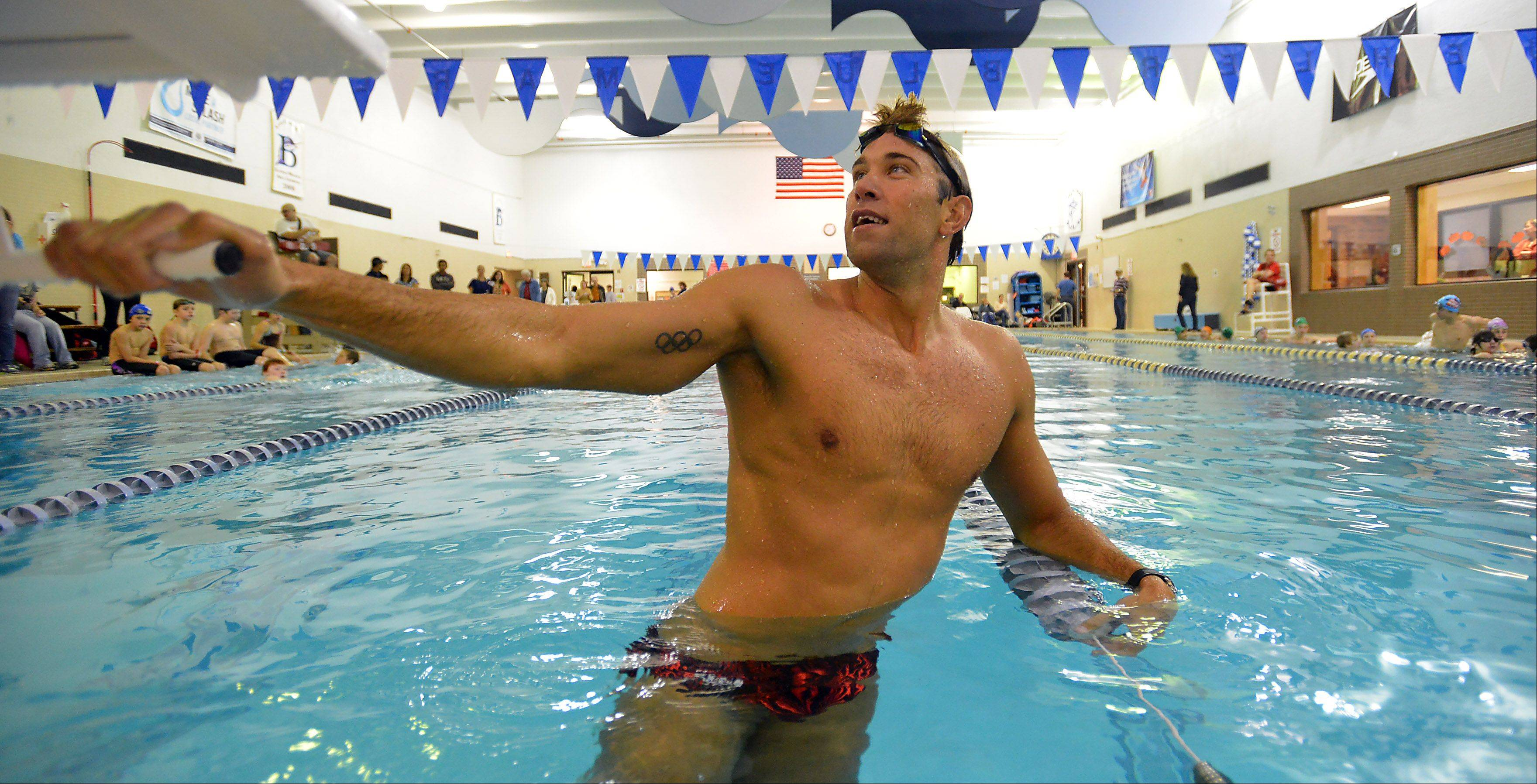 Olympic gold medalist Matt Grevers shows young swimmers the proper form of the butterfly stroke during a at Buehler YMCA in Palatine on Saturday.