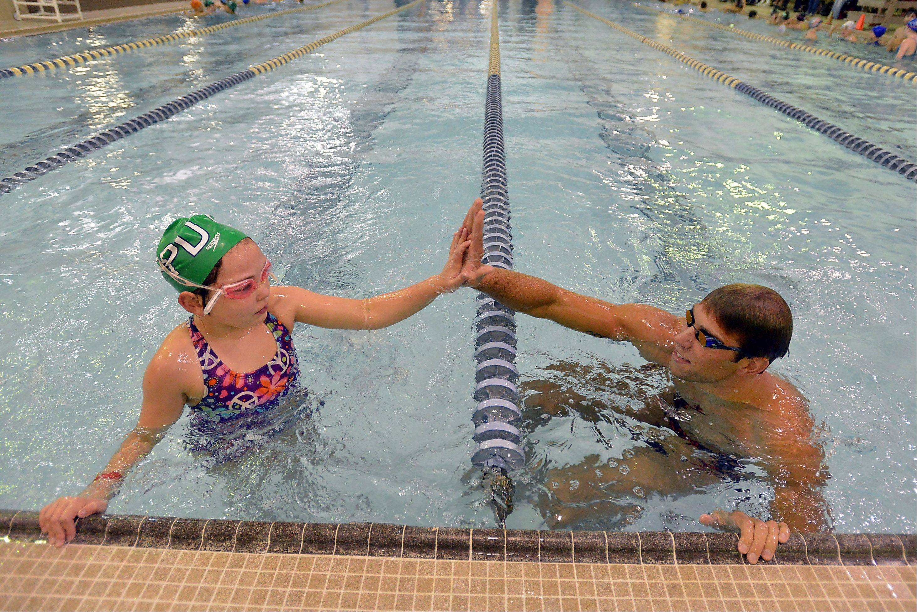 Olympic gold medalist Matt Grevers gives a high-five to Rose DeVooght, 8, of Palatine during a swimming clinic at the Buehler YMCA in Palatine on Saturday.