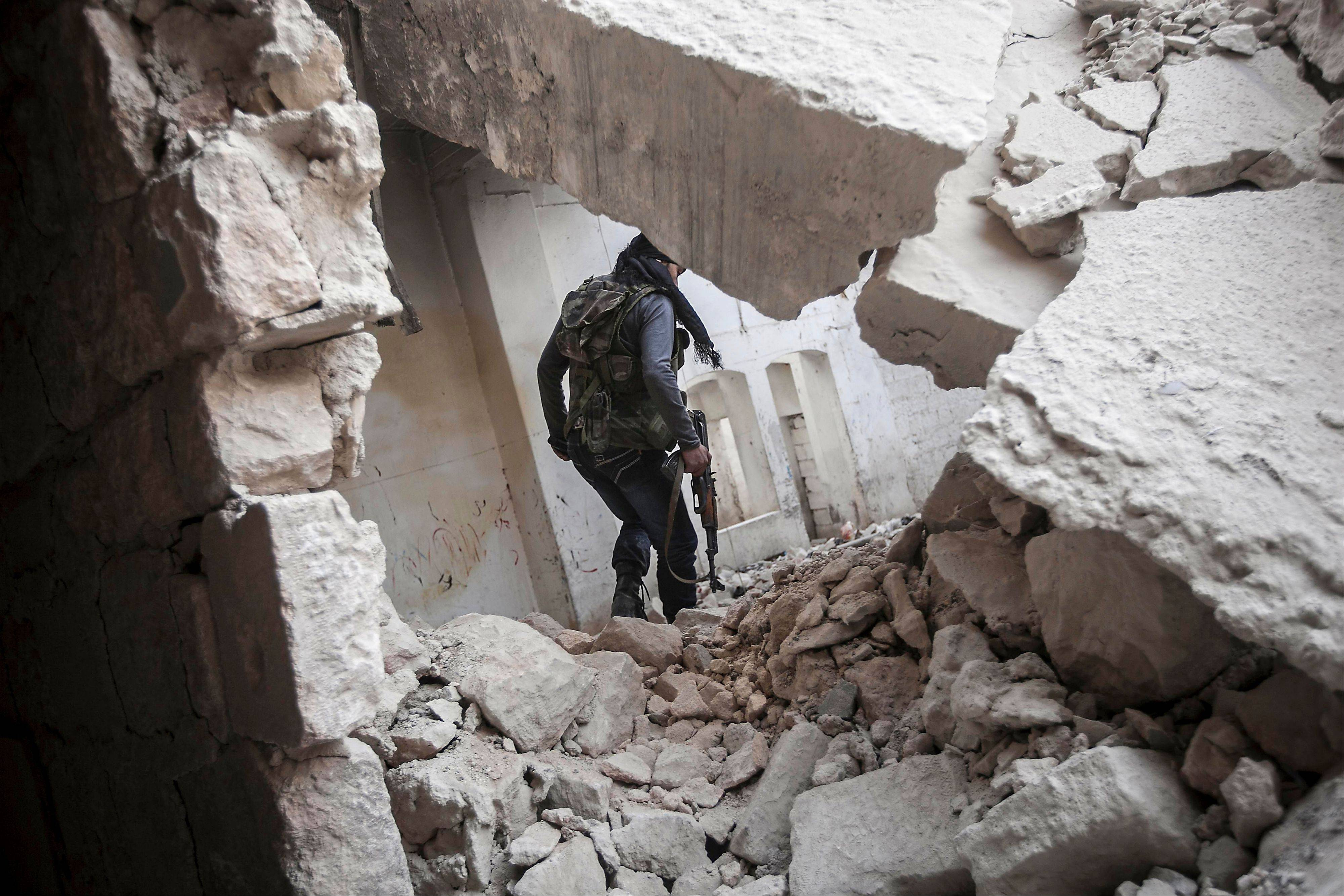 A rebel fighter walks Friday among the debris of damaged residential buildings after several days of intense fighting between rebel fighters and the Syrian army in the Karm al-Jebel neighborhood in Aleppo, Syria.