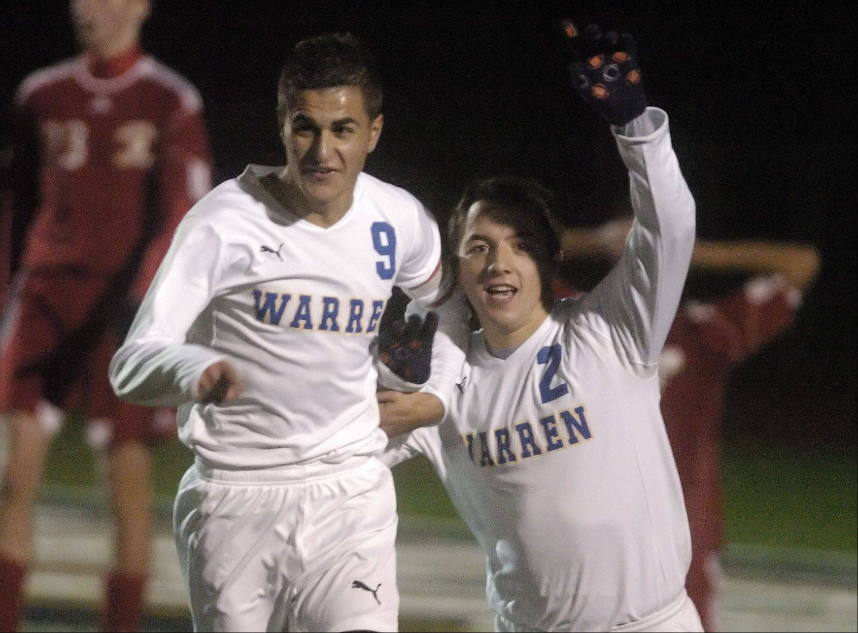 Daniel Szczepanek, left, and Tony Severini of Warren celebrate after a goal during the Blue Devils' championship effort against Naperville Central on Saturday night at Lincoln-Way North.