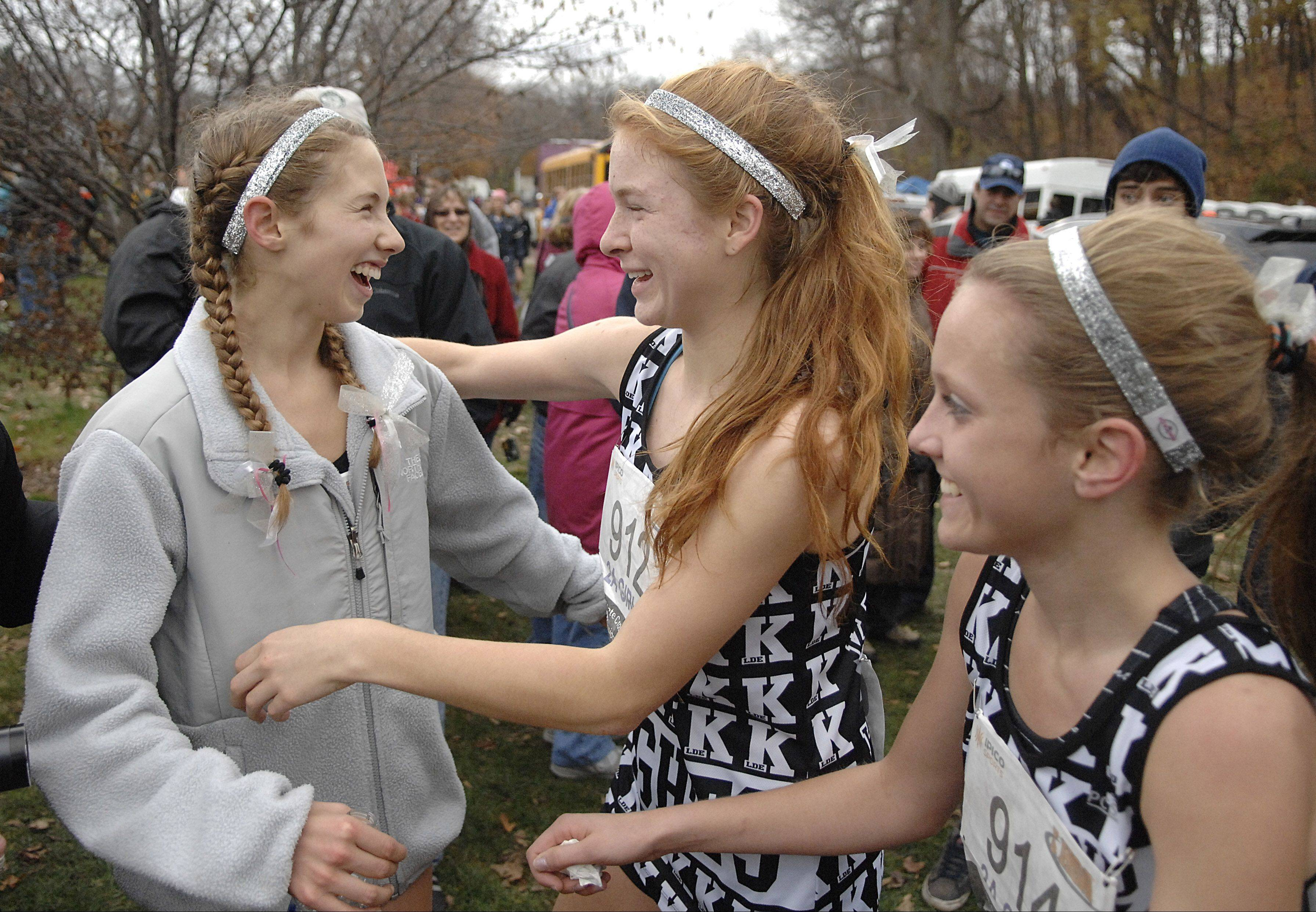 Kaneland's Victoria Clinton, left, gets hugs from teammates Aislinn Losdwig and Sydney Strang after winning the Class 2A state cross country championship in Peoria on Saturday.