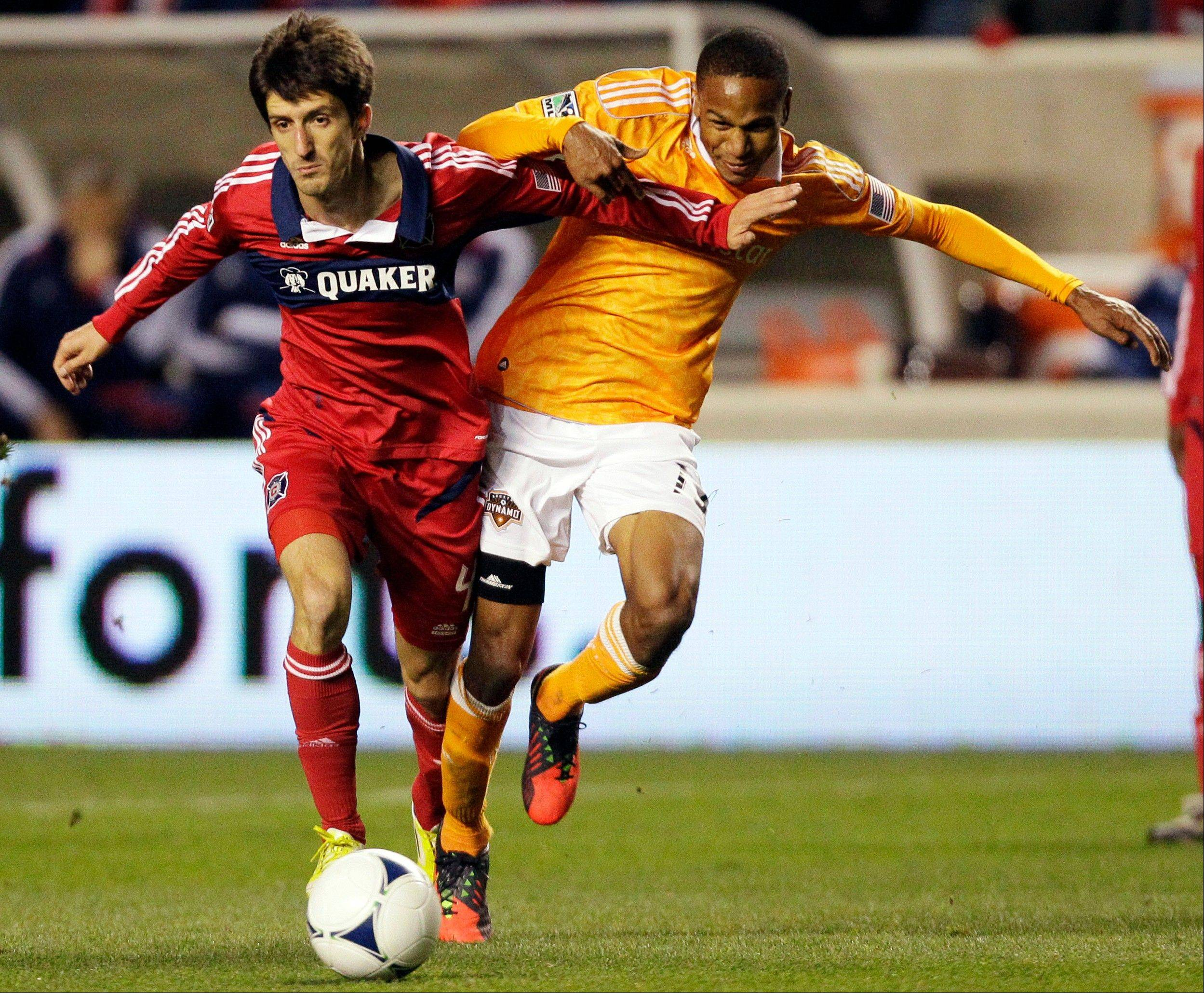 Chicago Fire midfielder Alvaro Fernandez, left, and Houston Dynamo midfielder Ricardo Clark (13) battle for the ball Saturday during the first half at Toyota Park.