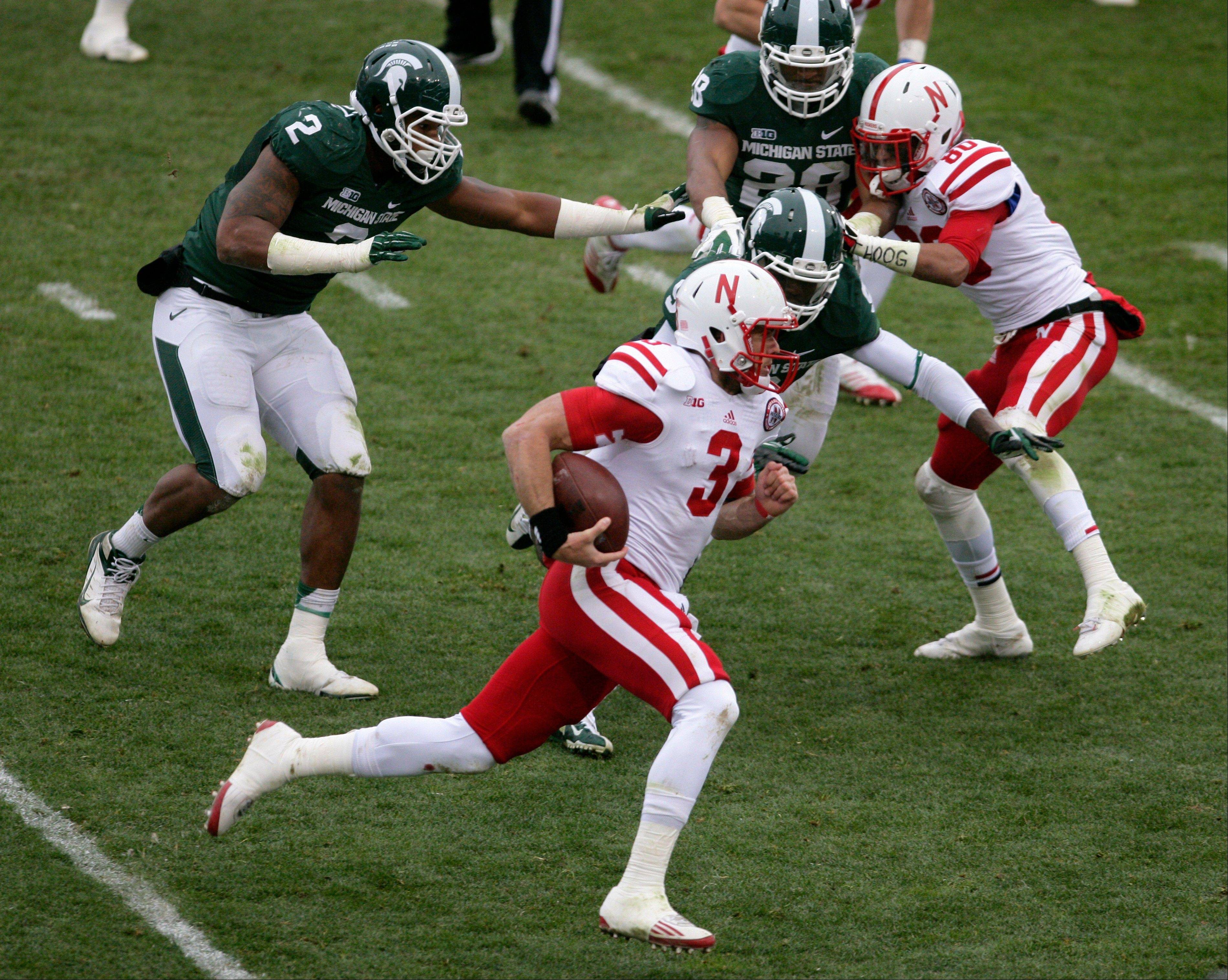 Nebraska quarterback Taylor Martinez gets past Michigan State's William Gholston (2), Isaiah Lewis, center, and Denicos Allen (28) Satuday for a 71-yard touchdown as Nebraska's Kenny Bell, right, blocks during the second quarter in East Lansing, Mich.