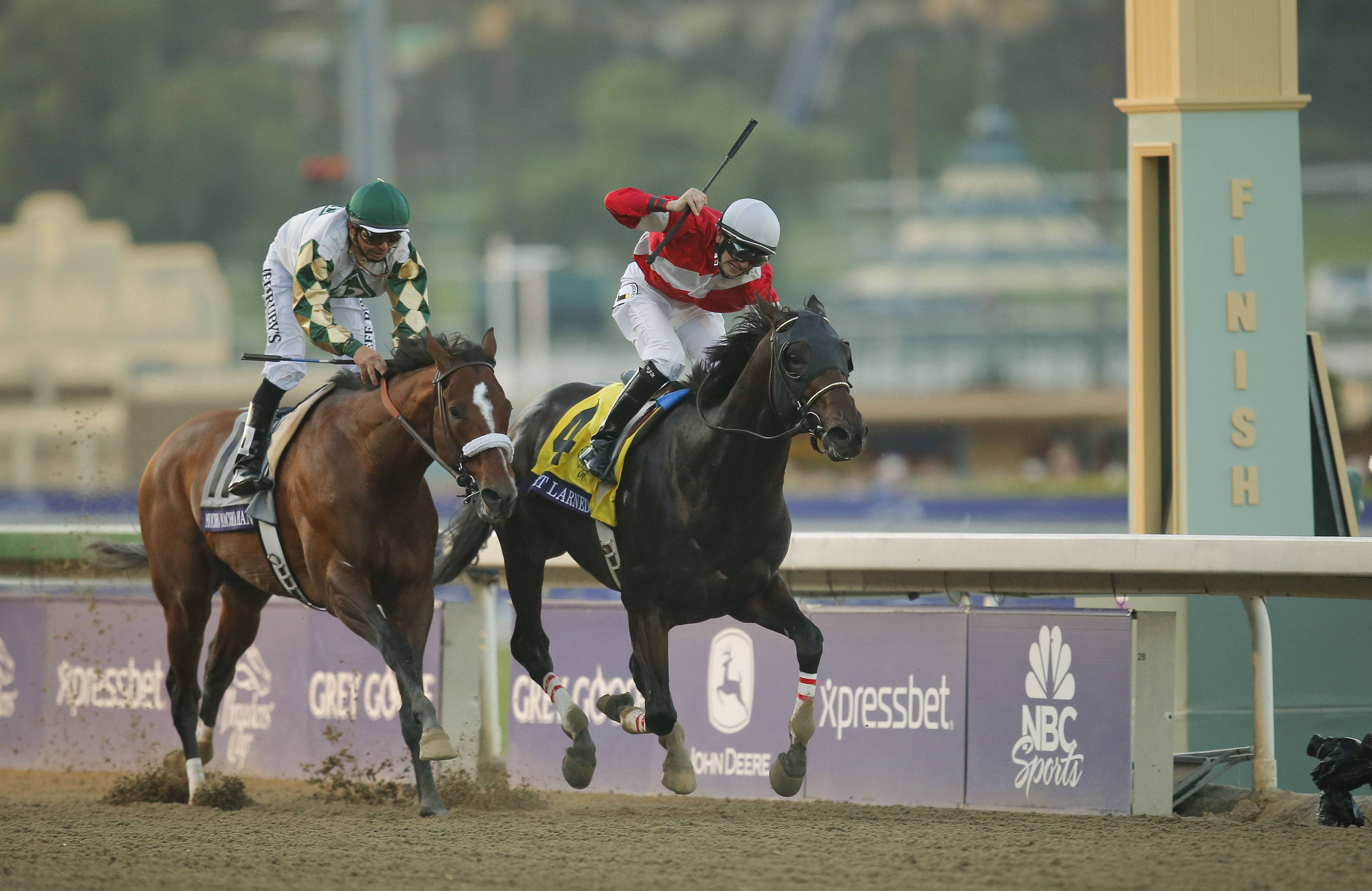 Brian Hernandez, atop Fort Larned, reacts as he crosses the finish line ahead of Mucho Macho Man, with Mike Smith atop, to win the Breeders' Cup Classic at Santa Anita Park in Arcadia, Calif.