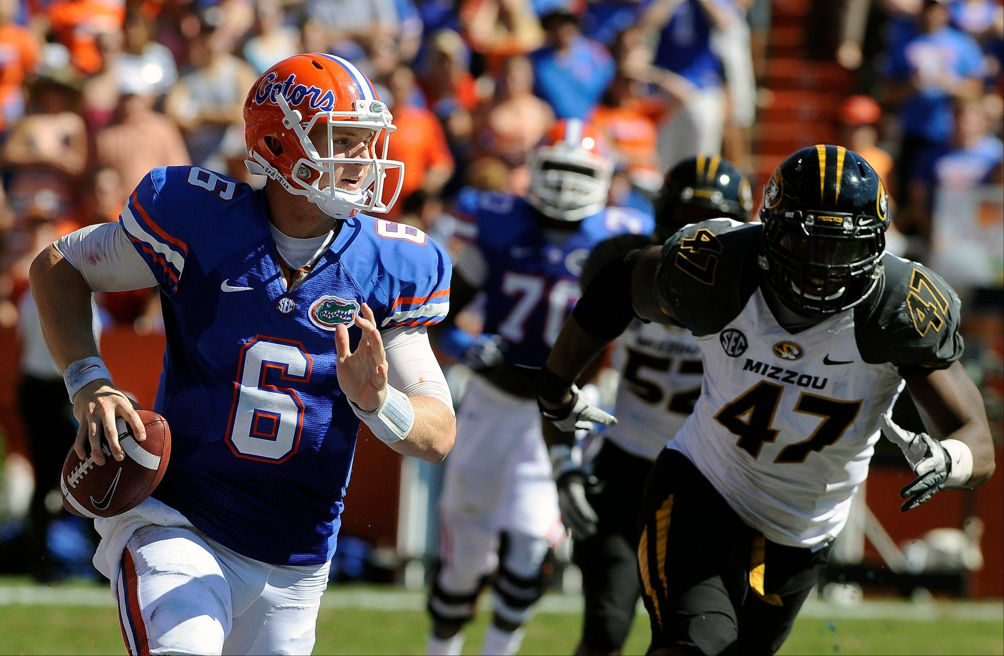 Florida quarterback Jeff Driskel scrambles with the ball as Missouri defensive lineman Kony Ealy tries to stop him Satudray during the first half.