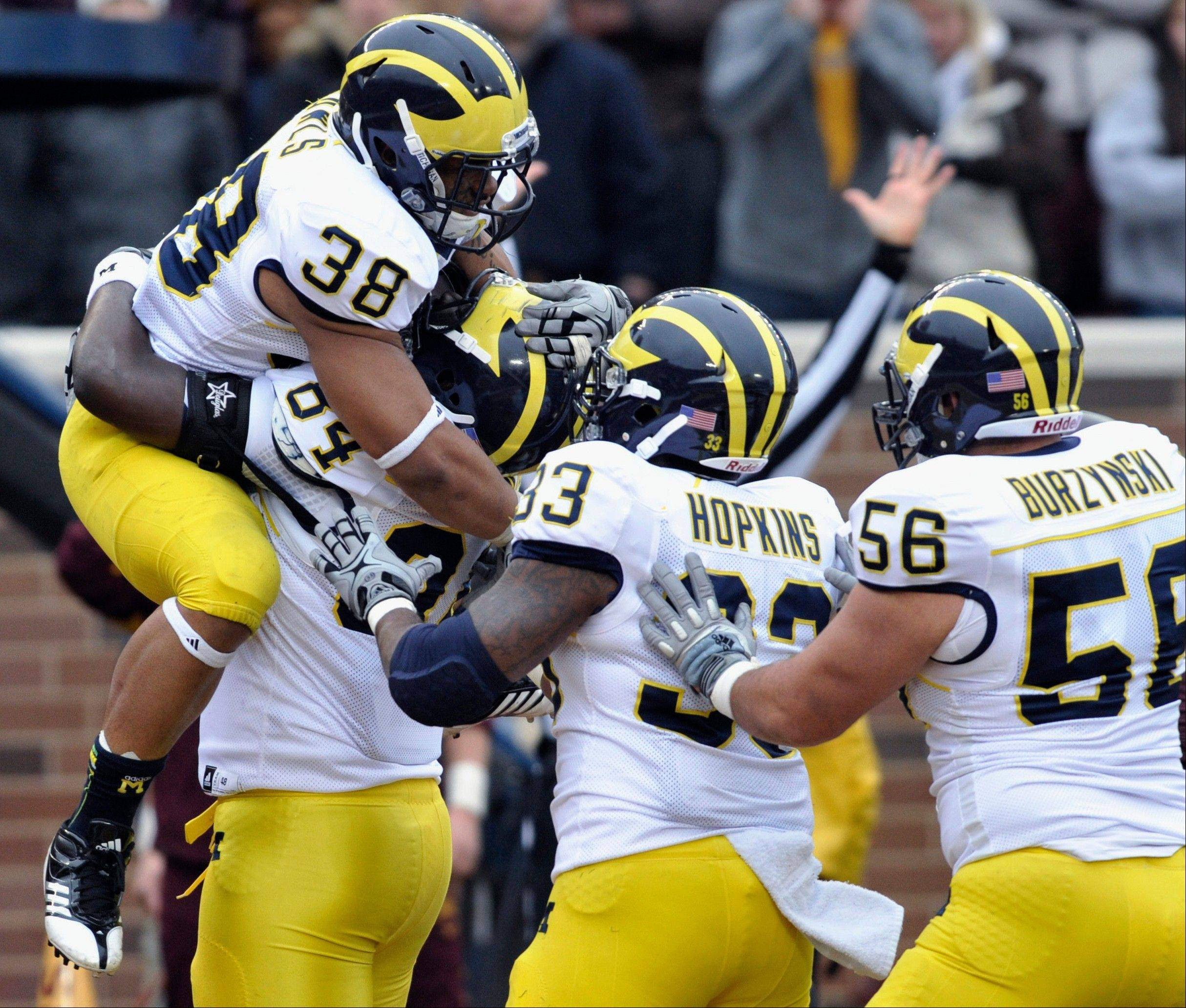 Michigan's A.J. Williams, second form left second, hoists running back Thomas Rawls (38) after Rawls scored a touchdown Saturday against Minnesota during the second quarter in Minneapolis. Michigan's Stephen Hopkins (33) and Joey Burzynski (56) join the celebration.