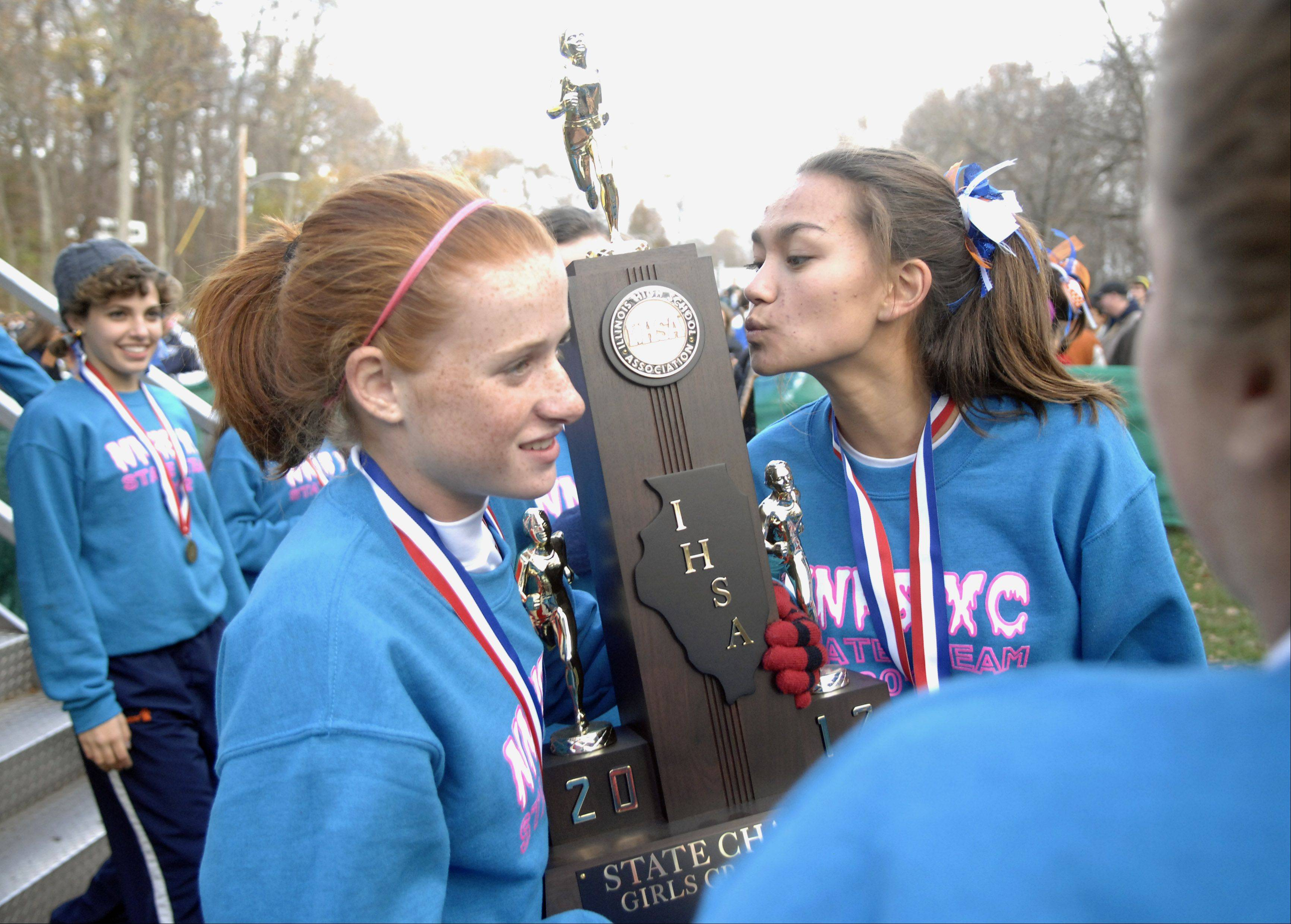 Naperville North's Allison Ray leans in to kiss the team's first place 3A trophy while carrying it with teammate Judy Pendergast during the awards ceremony at the cross country state finals in Peoria on Saturday, November 3.