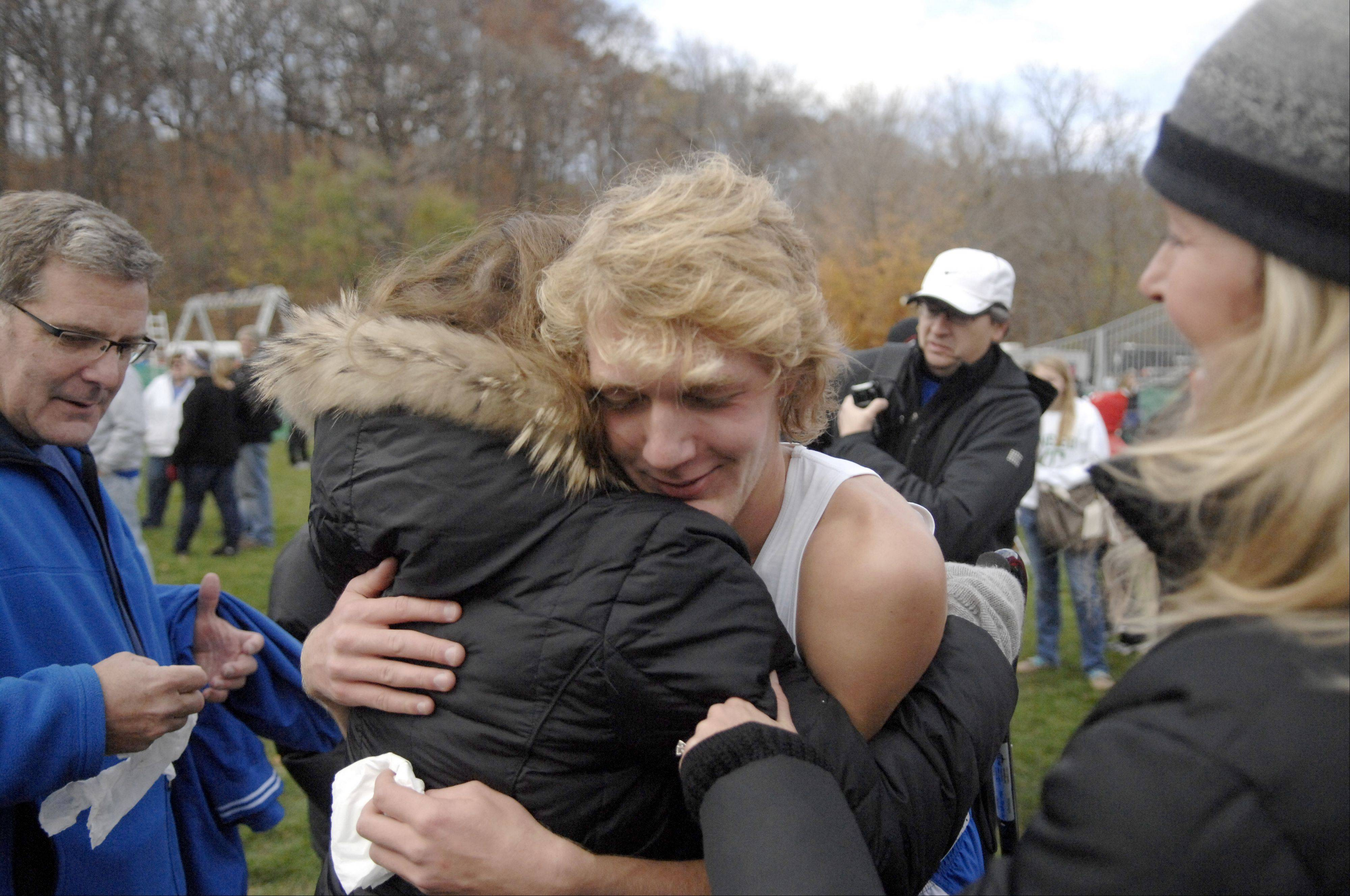 Glenbard South's John Wold gets a hug from grandmother Michele Mider of Chicago after winning the state cross country 2A final in Peoria on Saturday, November 3.