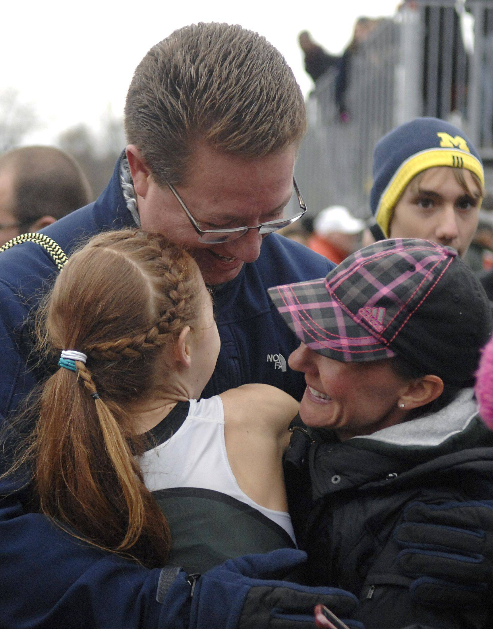 Madeline Perez is embraced by her parents, Ed and Joelle, after she took first place in the state 3A cross country final in Peoria on Saturday, November 3.
