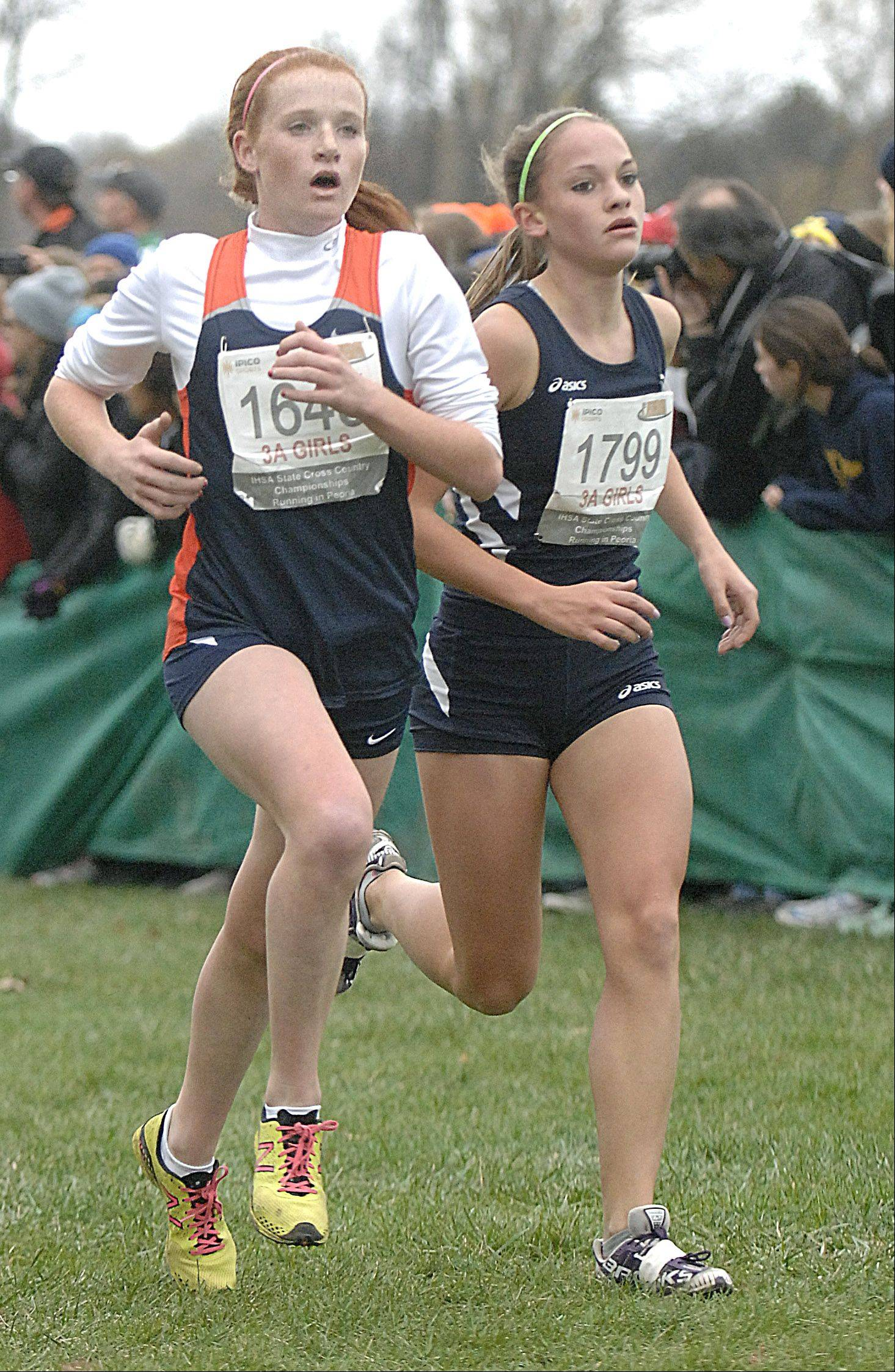 Naperville North's Judy Pendergast and Cary-Grove's Talia Duzey approach the finish line in the state cross country 3A final to take 23rd and 25th place respectively in Peoria on Saturday, November 3.