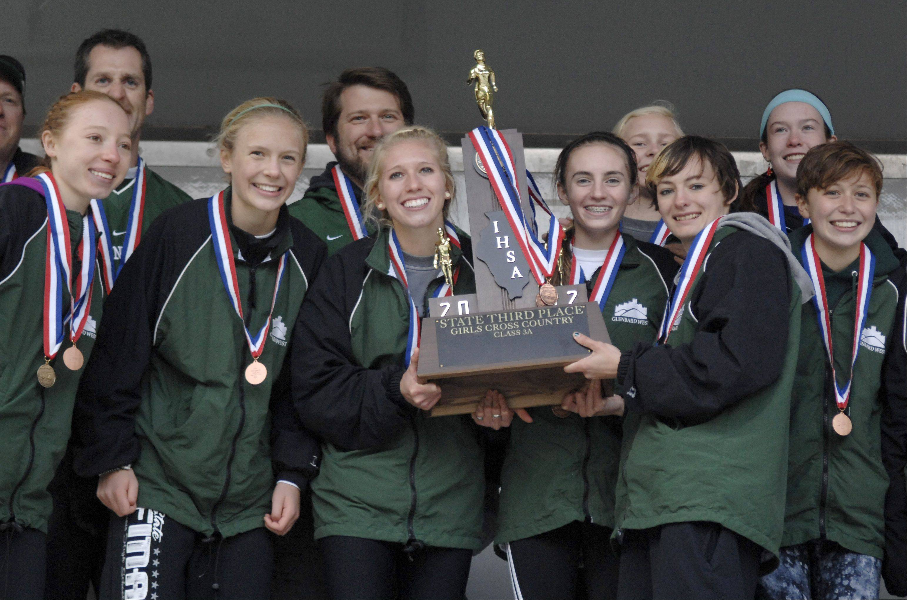 Glenbard West poses with their 3A third place trophy for fans at the cross country state finals in Peoria on Saturday, November 3.