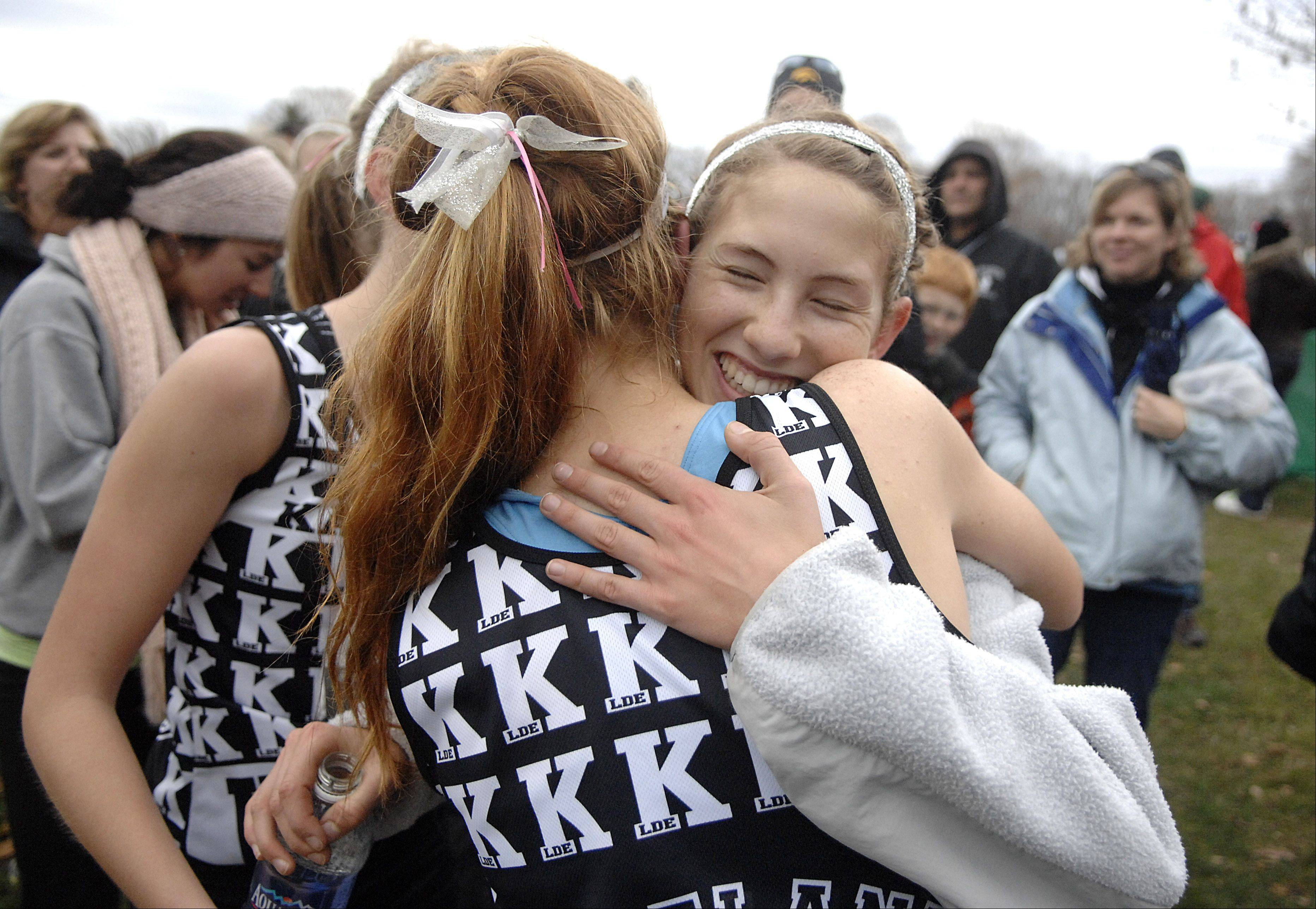 Kaneland's Victoria Clinton gets hugs from teammates Aislinn Losdwig and Sydney Strang after winning the 2A state cross country final in Peoria on Saturday, November 3.