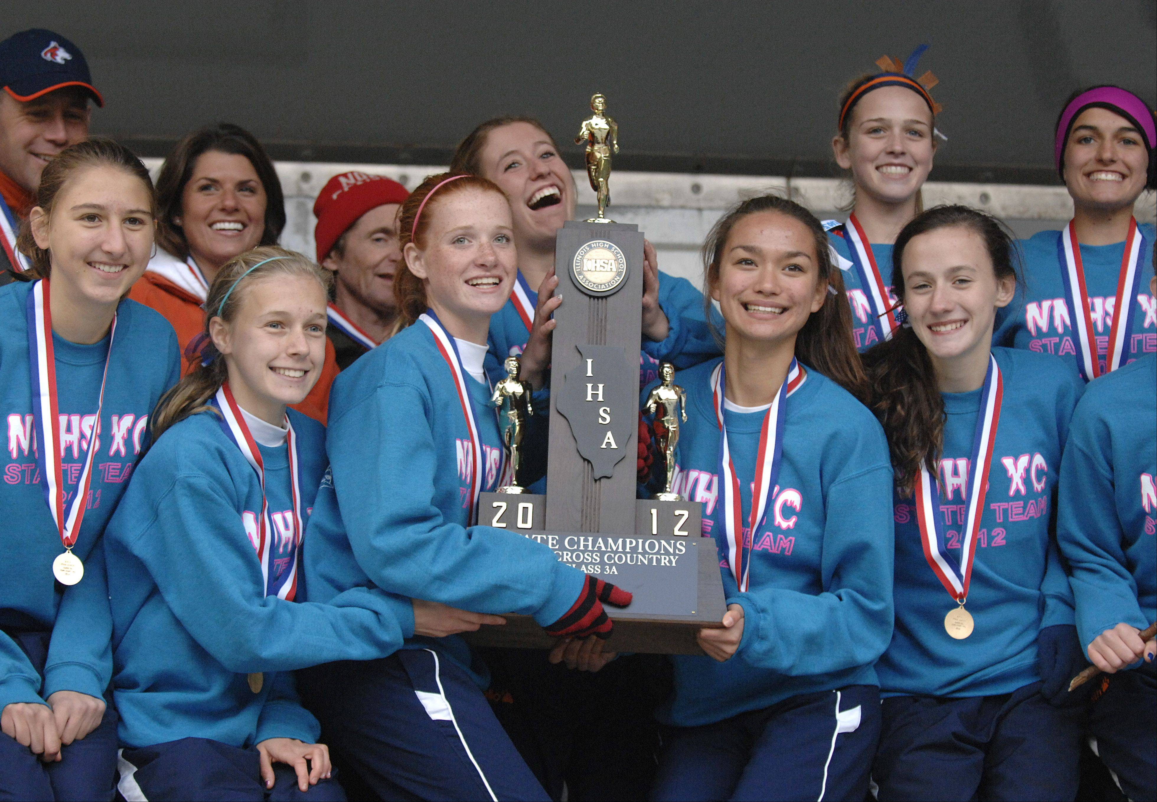 Naperville North poses for photos for fans with their 3A first place trophy at the cross country state finals in Peoria on Saturday, November 3.