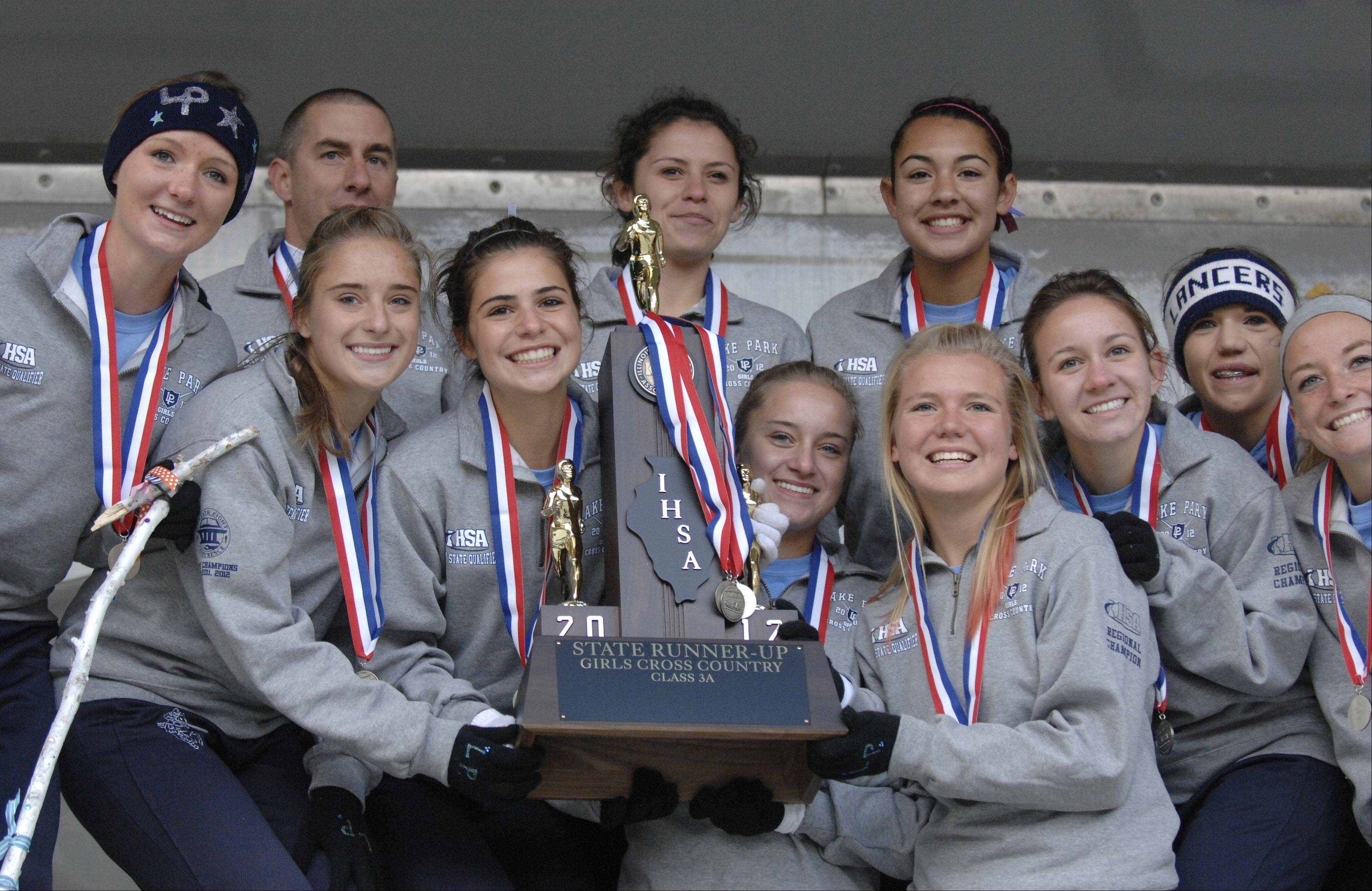 Lake Park poses with their 3A second place trophy for fans during the awards ceremony at the cross country state finals in Peoria on Saturday, November 3.